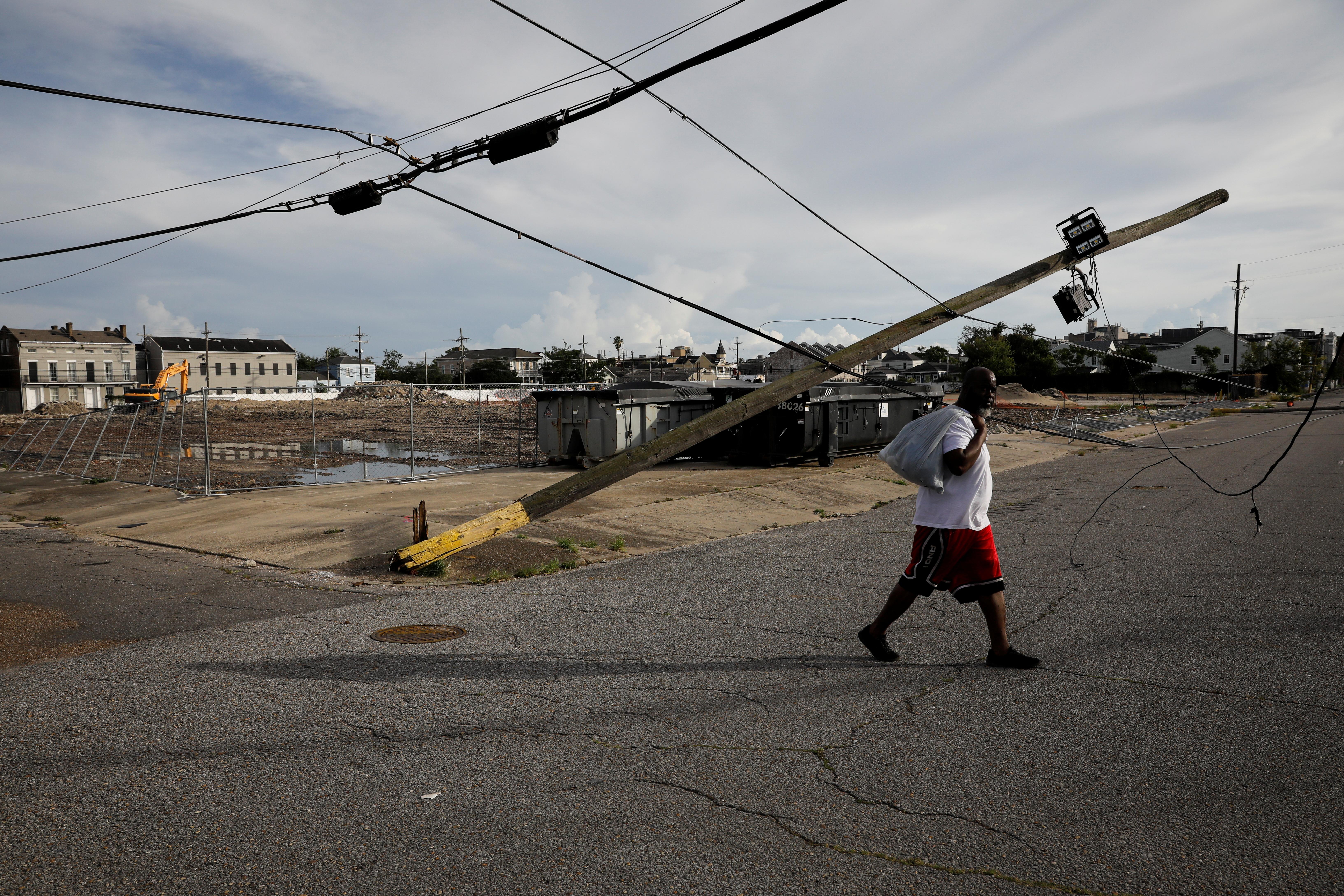 Чоловік проходить повз пошкодженої лінії електропередач на вулиці після того, як ураган Іда зійшов на берег у Луїзіані, у Новому Орлеані, штат Луїзіана, США 30 серпня 2021 р. REUTERS/Марко Белло