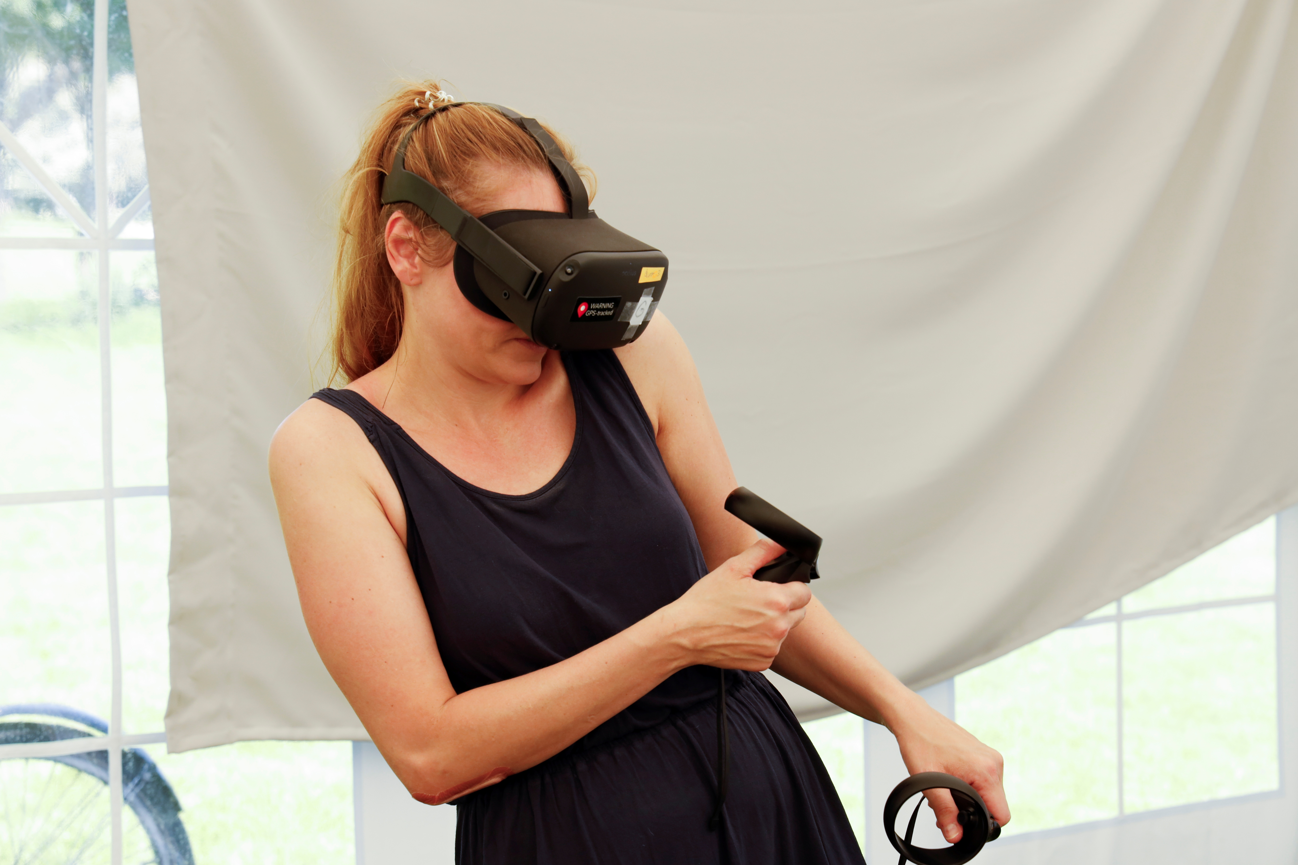 A participant takes part in an experiment, where researchers try to use virtual reality goggles to teach people about how virus infections spread, conducted in a park, amid the coronavirus disease (COVID-19) pandemic, in Copenhagen, Denmark, June 6, 2021. Picture taken June 6, 2021. REUTERS/Tim Barsoe