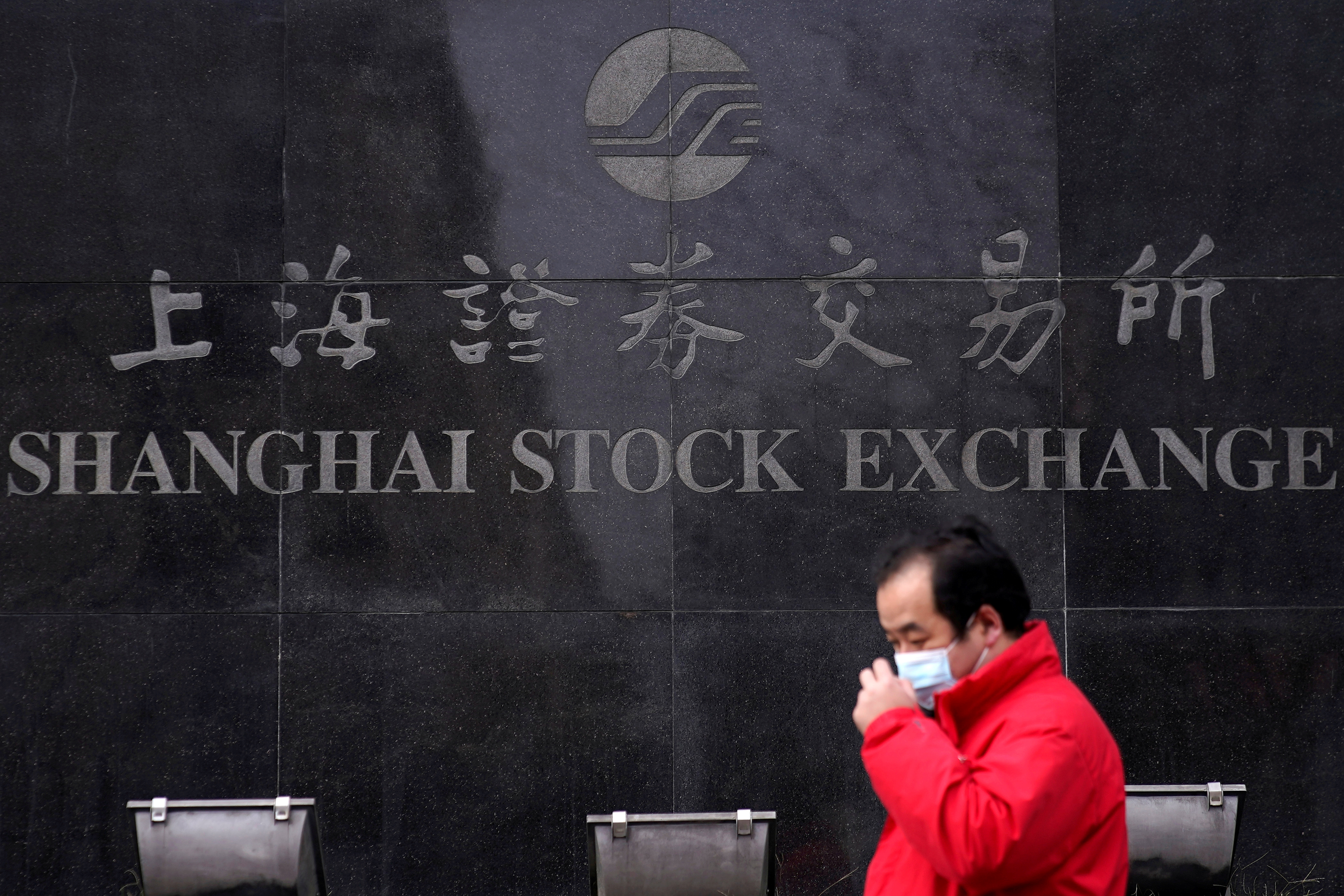 A man wearing a mask walks by the Shanghai Stock Exchange building at the Pudong financial district in Shanghai, China, February 3, 2020. REUTERS/Aly Song