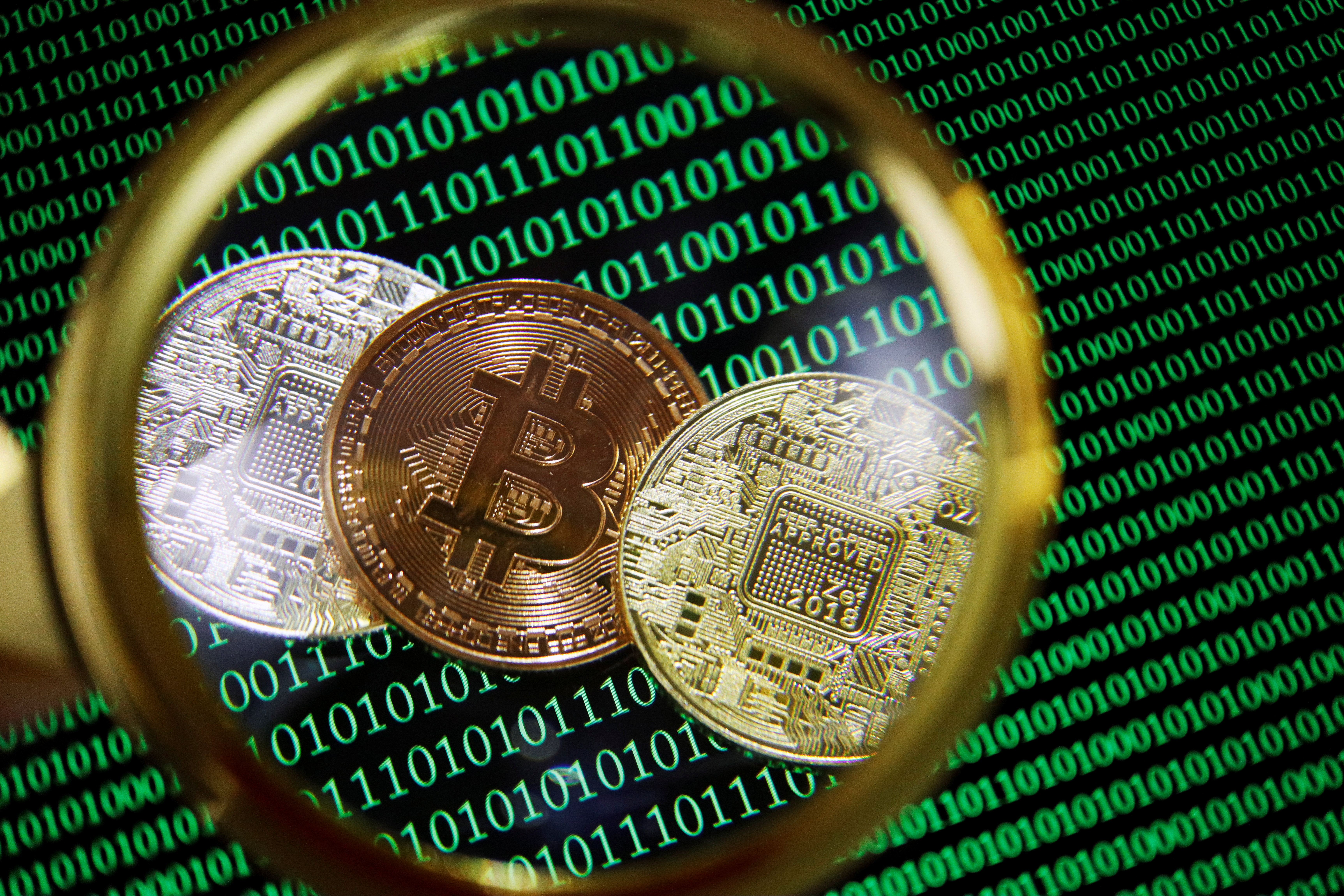 Representations of Bitcoin and other cryptocurrencies on a screen showing binary codes are seen through a magnifying glass in this illustration picture taken September 27, 2021. REUTERS/Florence Lo/Illustration