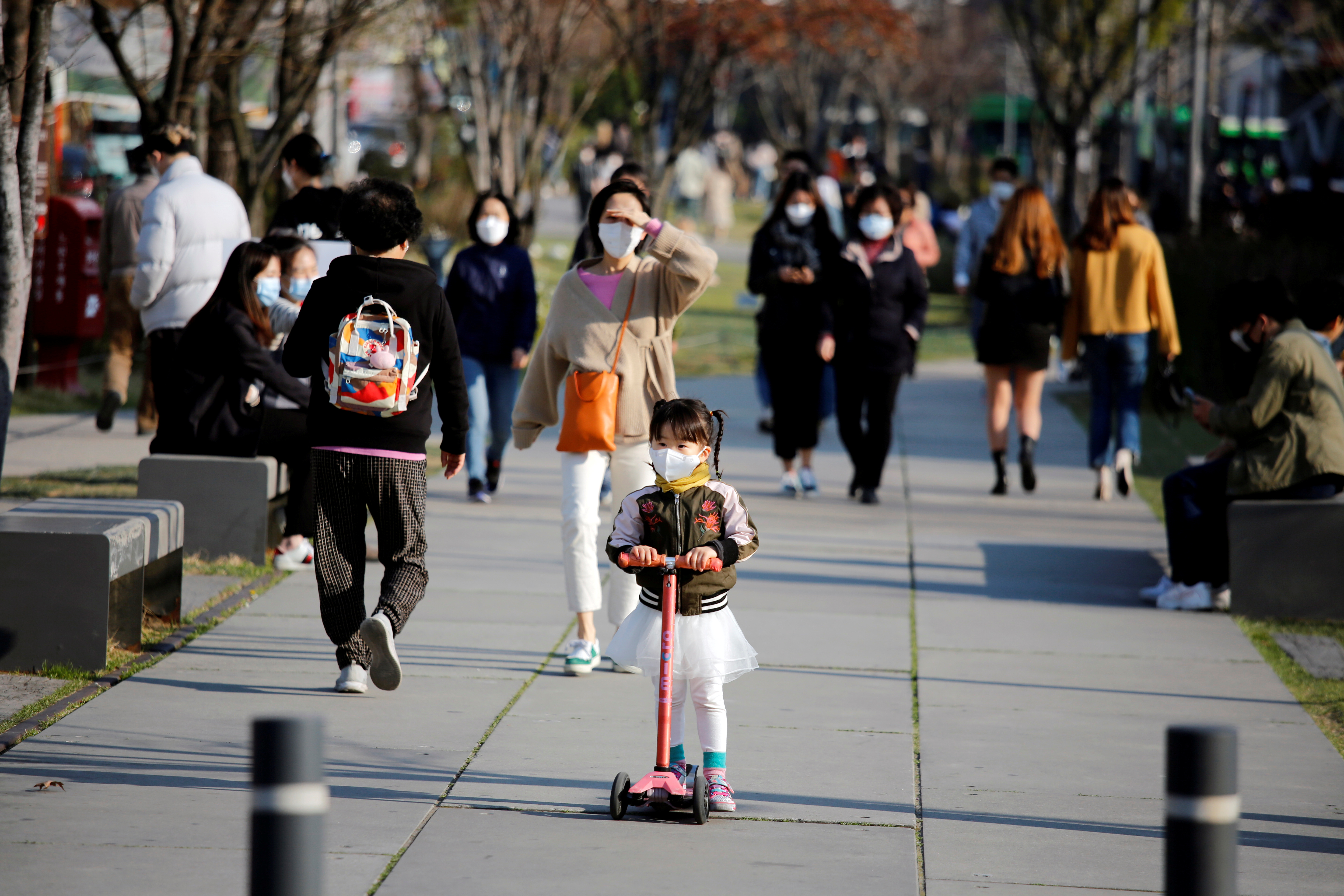 A girl wearing a protective face mask to prevent contracting the coronavirus disease (COVID-19) rides a toy kick scooter at a park in Seoul, South Korea, April 3, 2020.    REUTERS/Heo Ran