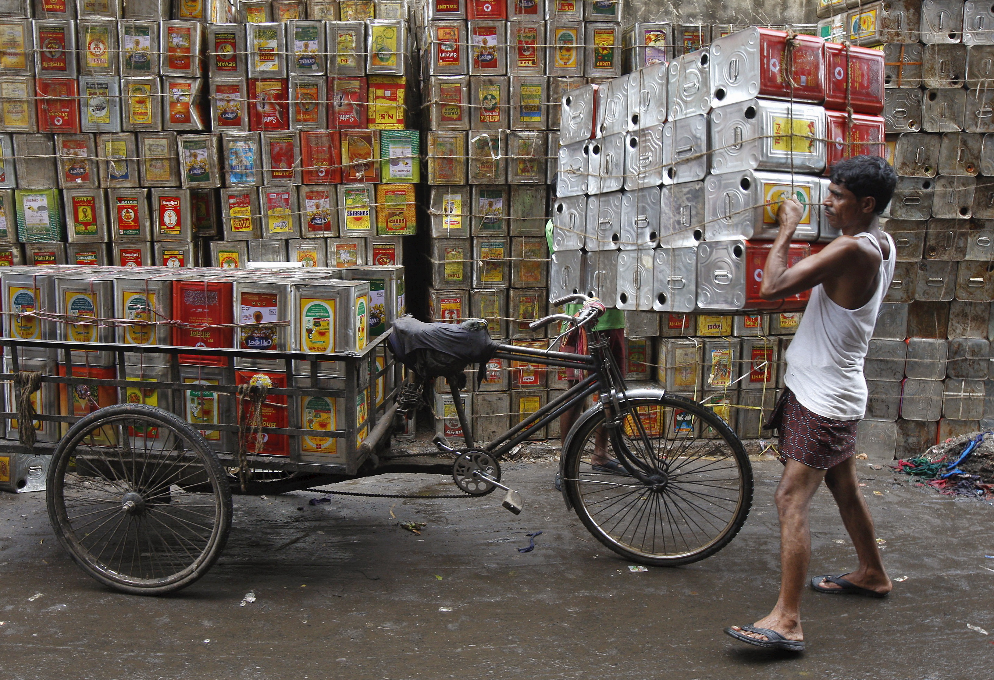 A man loads empty containers of edible oil onto a tricycle at a roadside in Kolkata, India, August 27, 2015. REUTERS/Rupak De Chowdhuri