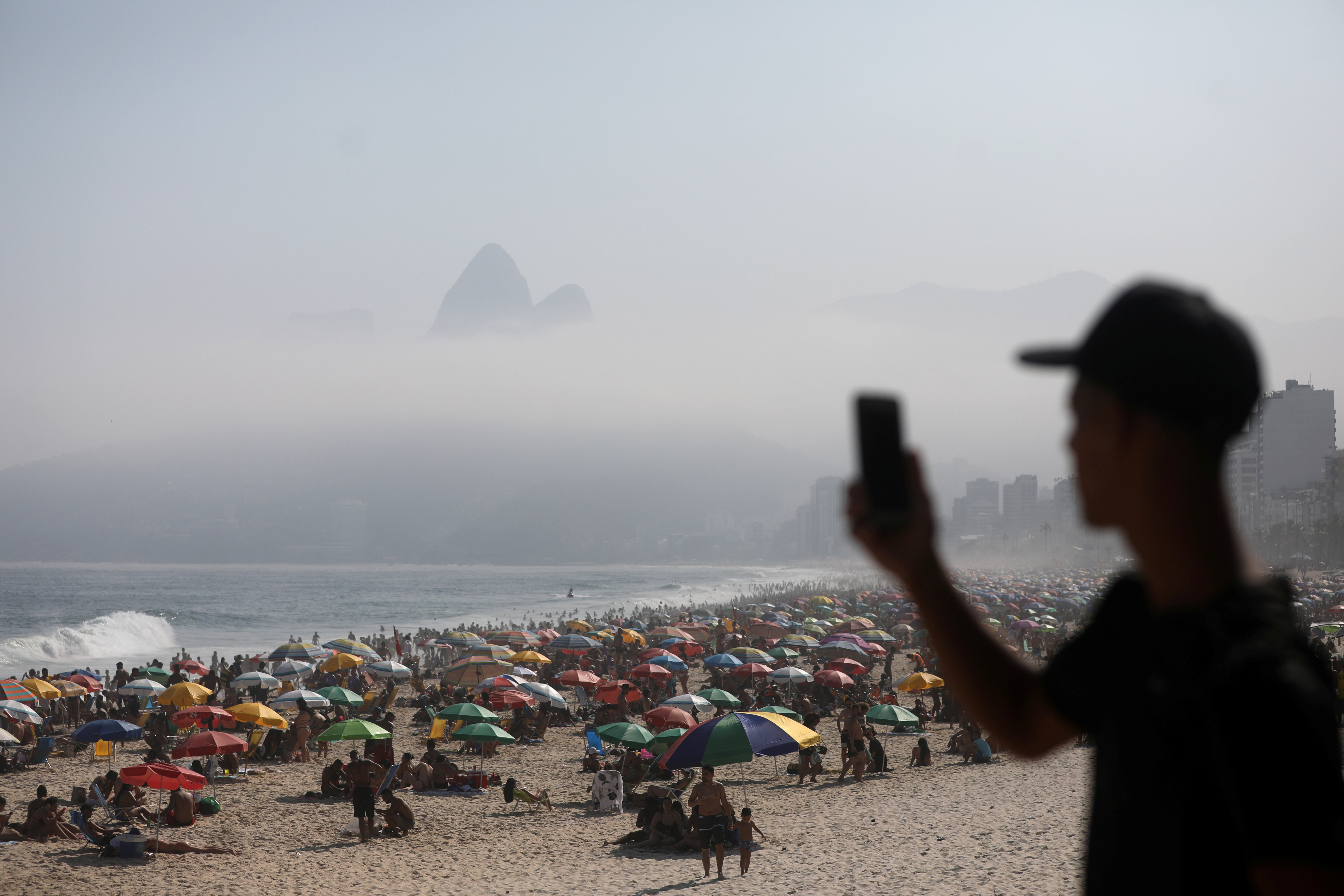 A man uses his phone as people enjoy at Ipanema beach, amid the coronavirus disease (COVID-19) outbreak, in Rio de Janeiro, Brazil September 6, 2020. REUTERS/Pilar Olivares
