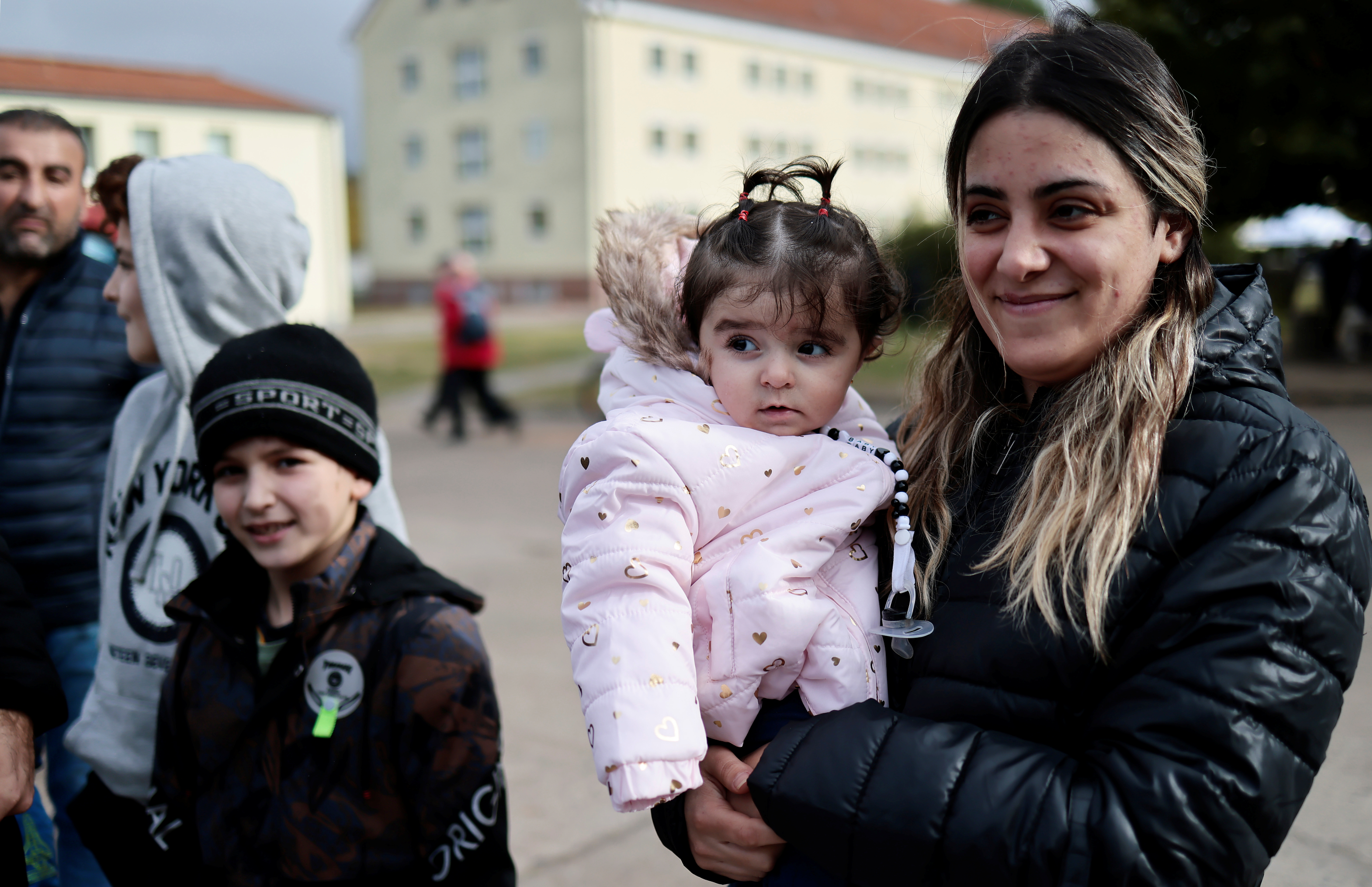 A woman holds her kid at a camp in Eisenhuettenstadt, Germany, October 14, 2021. REUTERS/Hannibal Hanschke