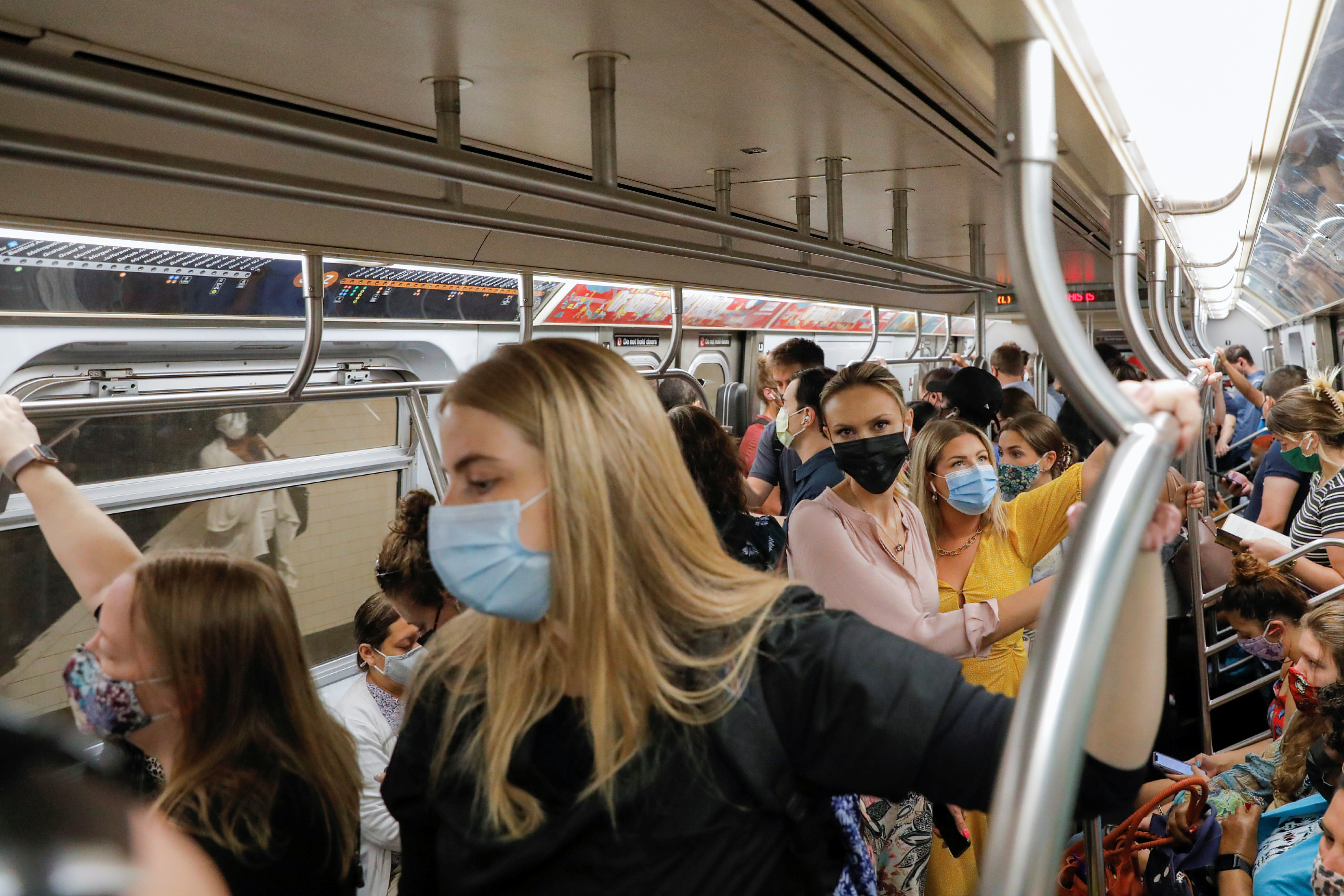 People wear masks while riding on the subway as cases of the infectious coronavirus Delta variant continue to rise in New York City, New York, U.S., August 2, 2021. REUTERS/Andrew Kelly
