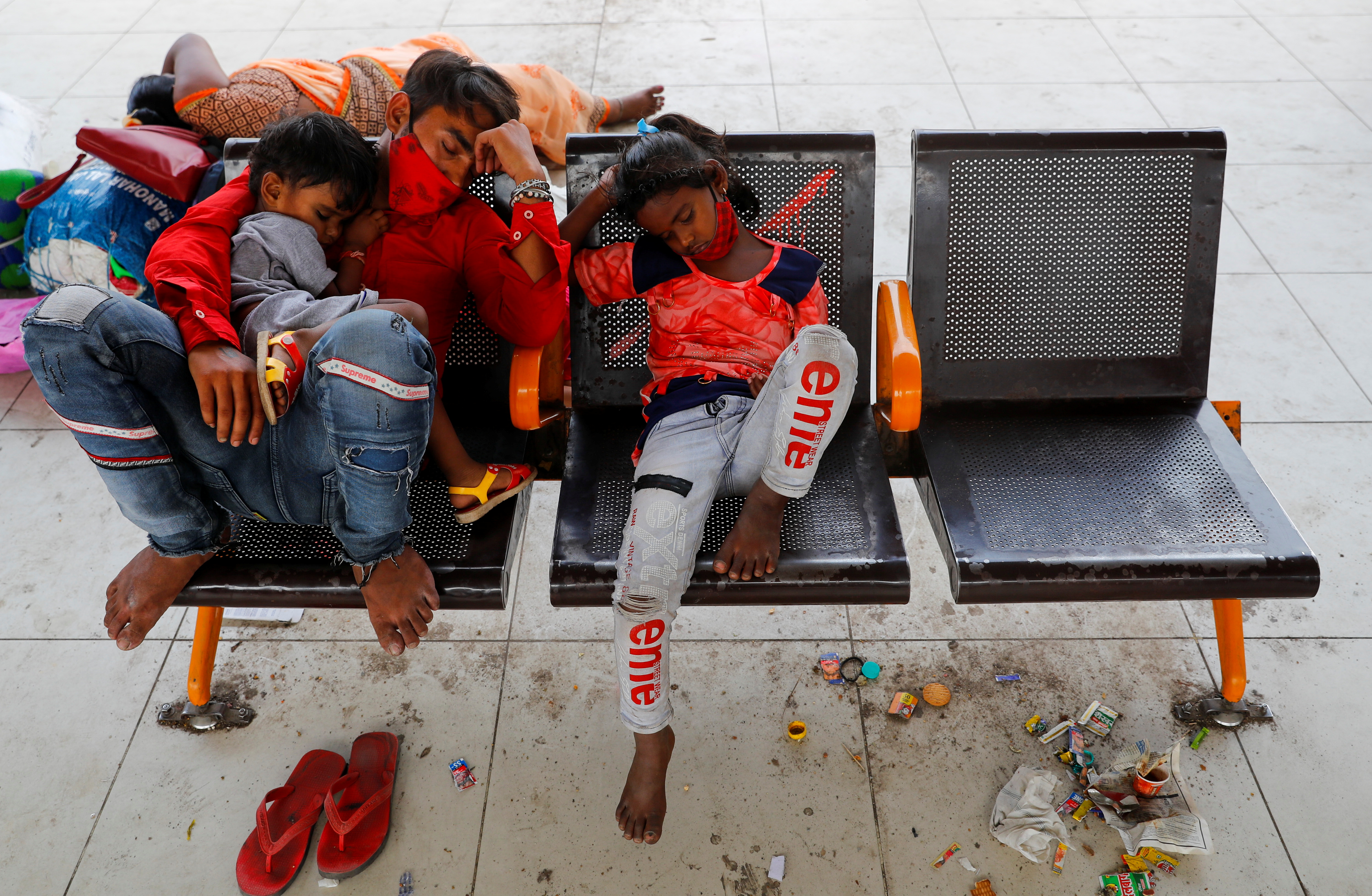 A migrant worker and his children sleep at a bus station as they wait to return to their village, after Delhi government ordered a six-day lockdown to limit the spread of the coronavirus disease (COVID-19), in Ghaziabad on the outskirts of New Delhi, India, April 20, 2021. REUTERS/Adnan Abidi