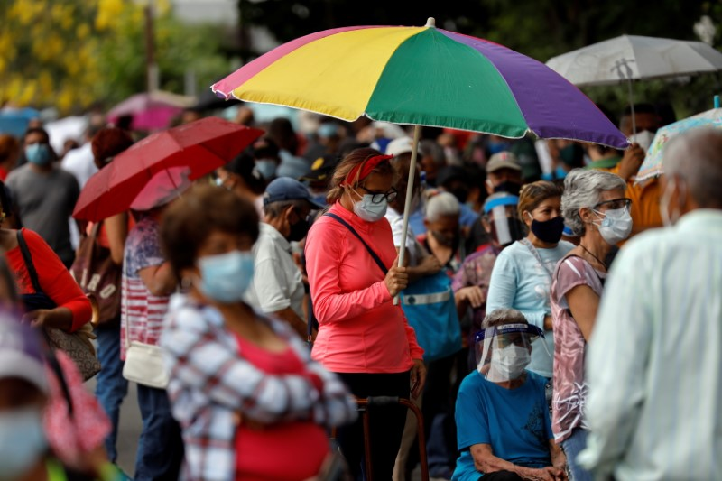 A woman with an umbrella waits with her mother on a street outside the Regional Government Health Corporation turned into a mass vaccination centre to receive their first dose of Russia's Sputnik V vaccine against the coronavirus disease (COVID-19), in Maracay, Venezuela June 8, 2021. REUTERS/Leonardo Fernandez Viloria