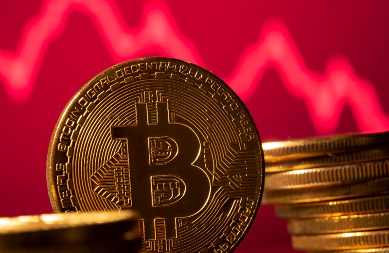 A representation of virtual currency Bitcoin is seen in front of a stock graph in this illustration taken May 19, 2021. REUTERS/Dado Ruvic/Illustration