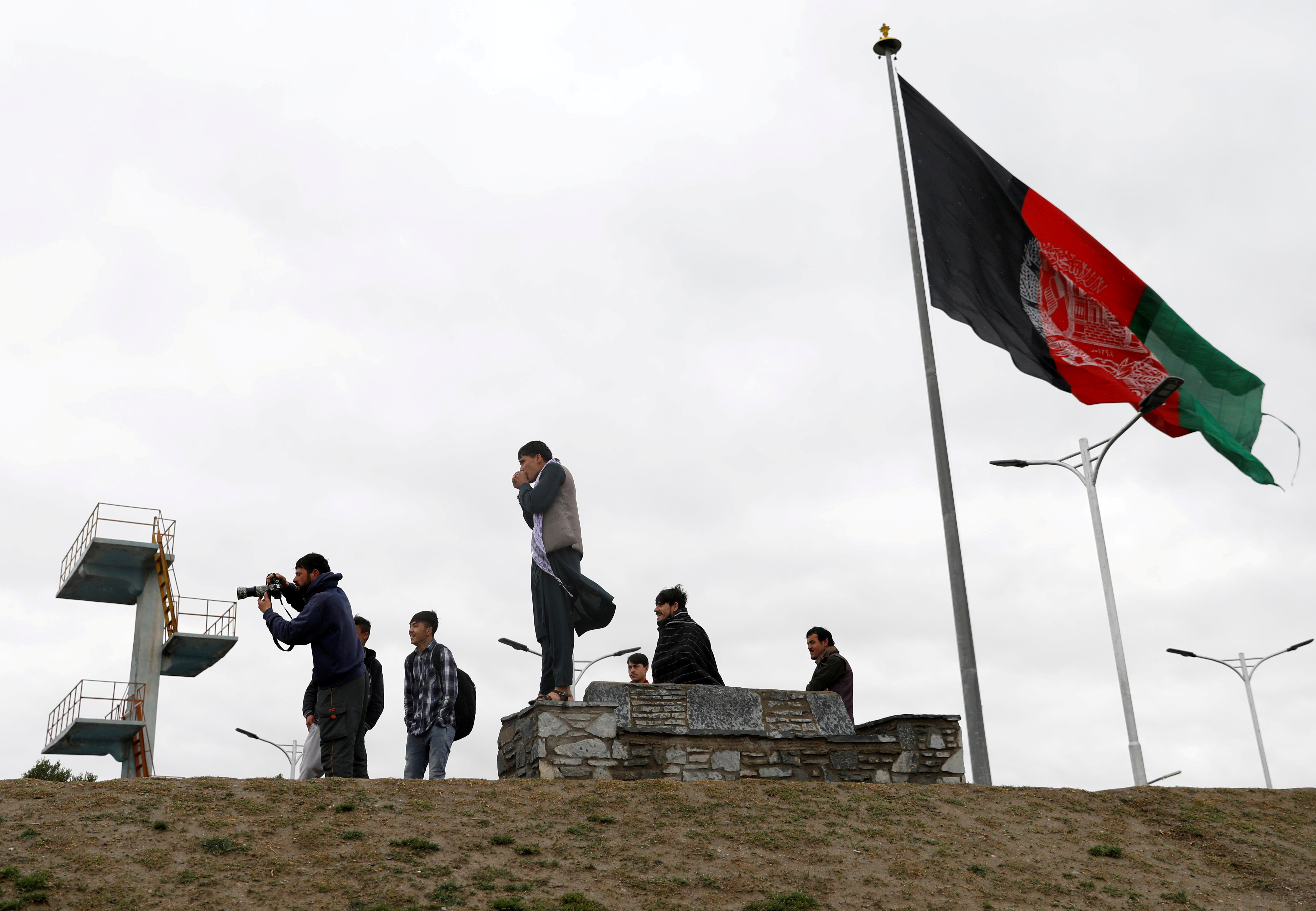 Youths take pictures next to an Afghan flag on a hilltop overlooking Kabul, Afghanistan, April 15, 2021. REUTERS/Mohammad Ismail/File Photo