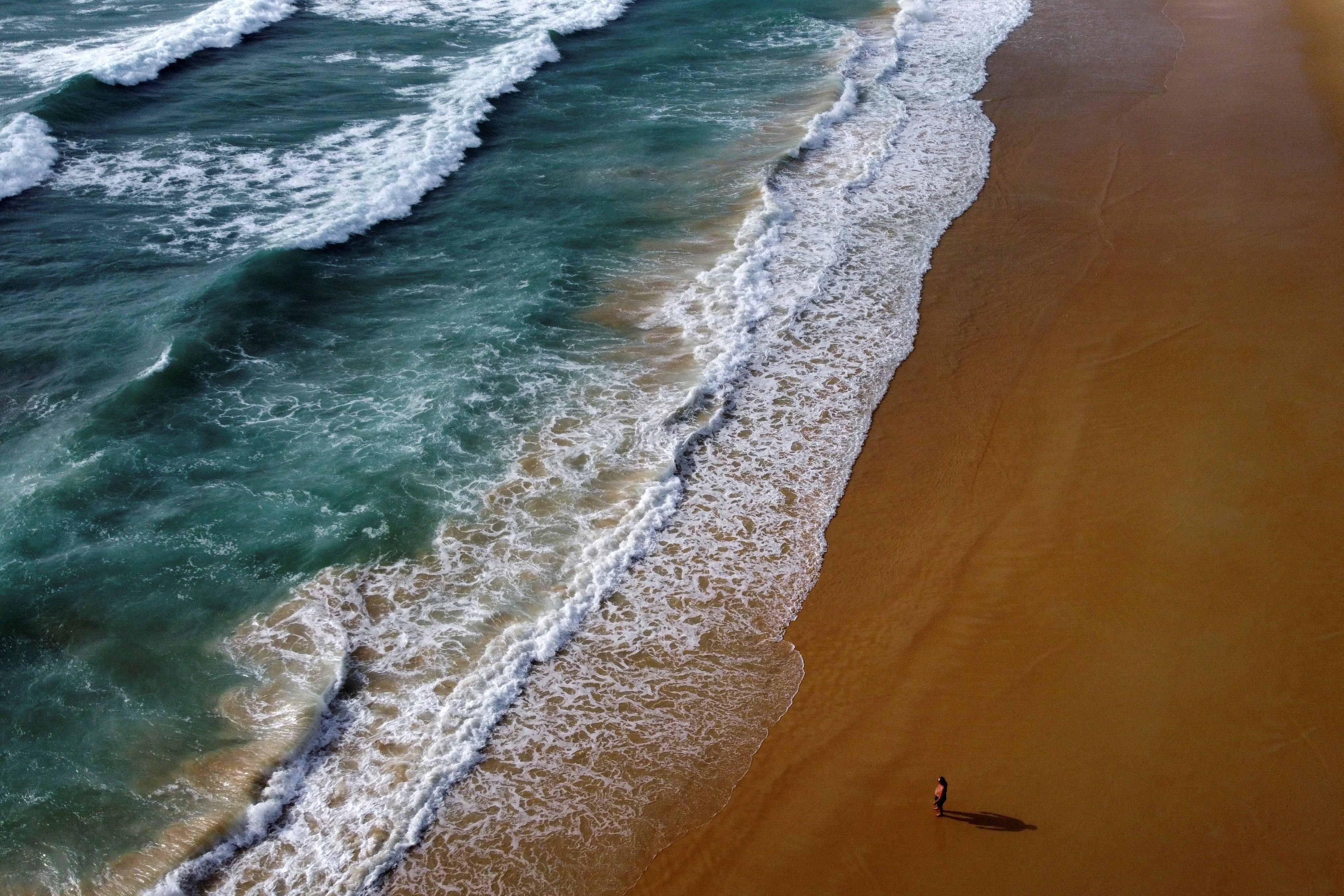 A man walks at the empty Karon beach on Phuket Island, Thailand in April 1, 2021. Picture taken April 1, 2021 with a drone. REUTERS/Jorge Silva/File Photo