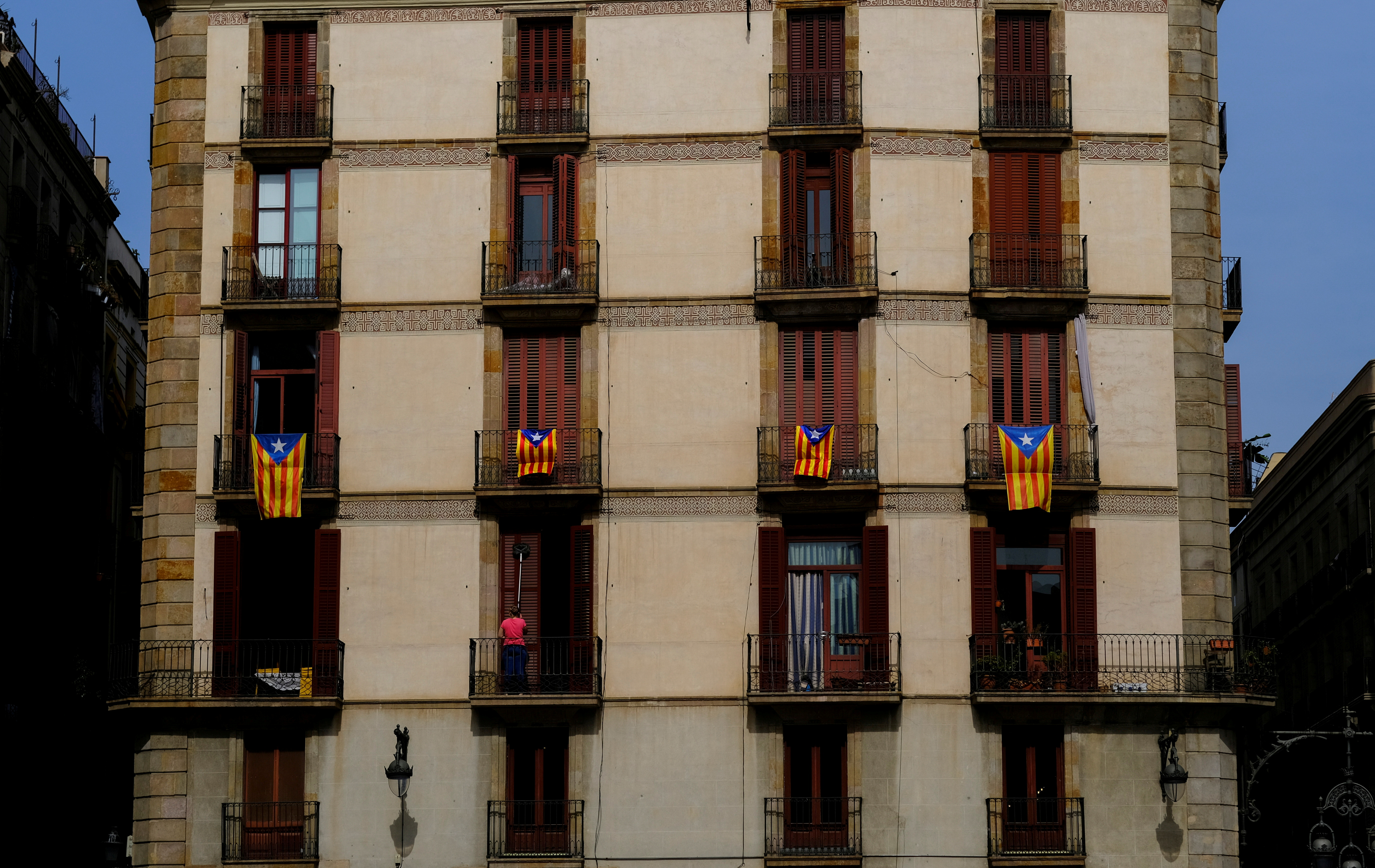 A woman cleans the windows of a house underneath Esteladas (Catalan separatist flags) hanging on balconies at Sant Jaume Square, a day before a meeting between the Catalan regional President Pere Aragones and the Spanish Prime Minister Pedro Sanchez at Palau de la Generalitat in Barcelona, Spain September 14, 2021. REUTERS/Nacho Doce