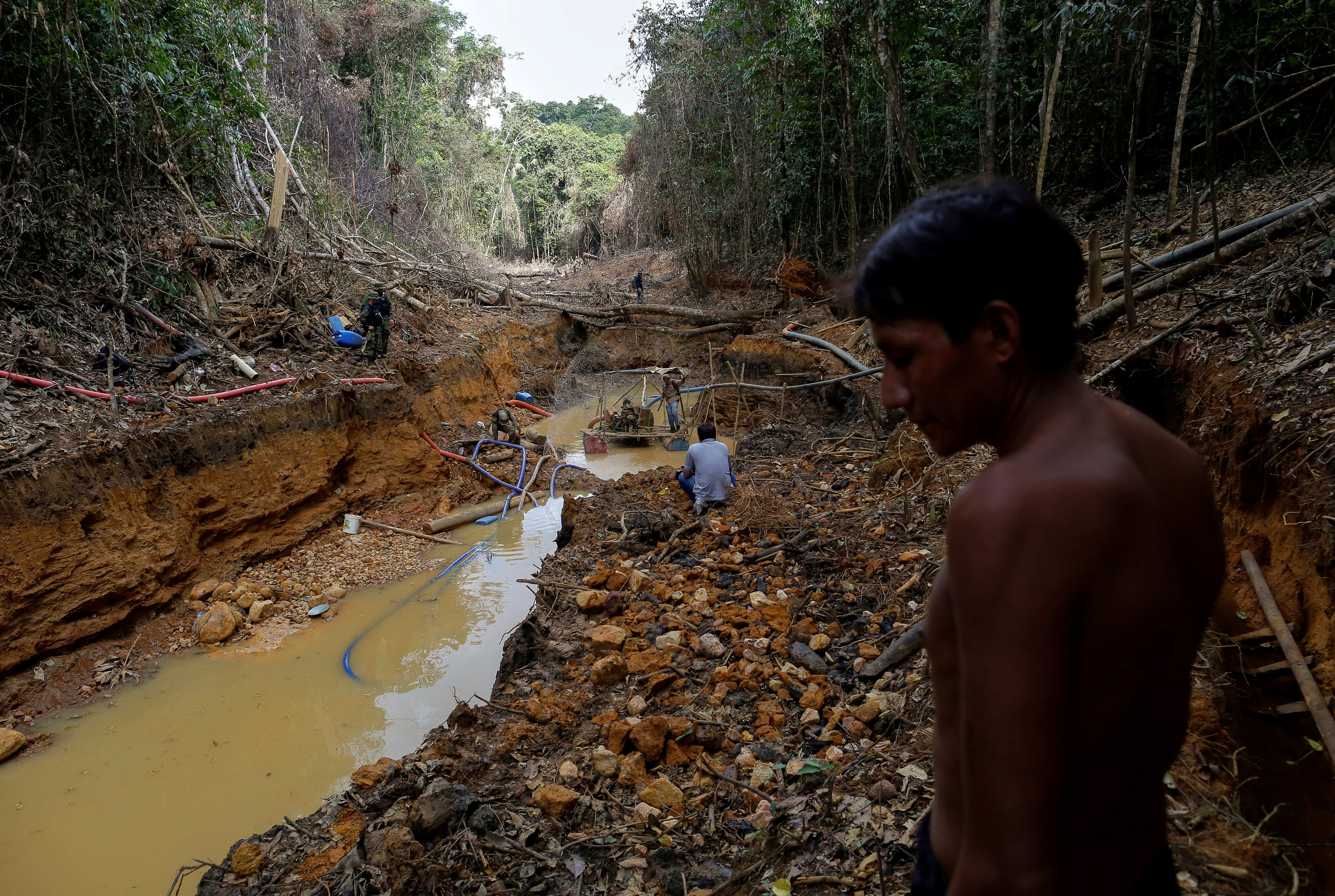 A Yanomami indian follows agents of Brazil's environmental agency in a gold mine during an operation against illegal gold mining on indigenous land, in the heart of the Amazon rainforest, in Roraima state, Brazil April 17, 2016. REUTERS/Bruno Kelly/File Photo