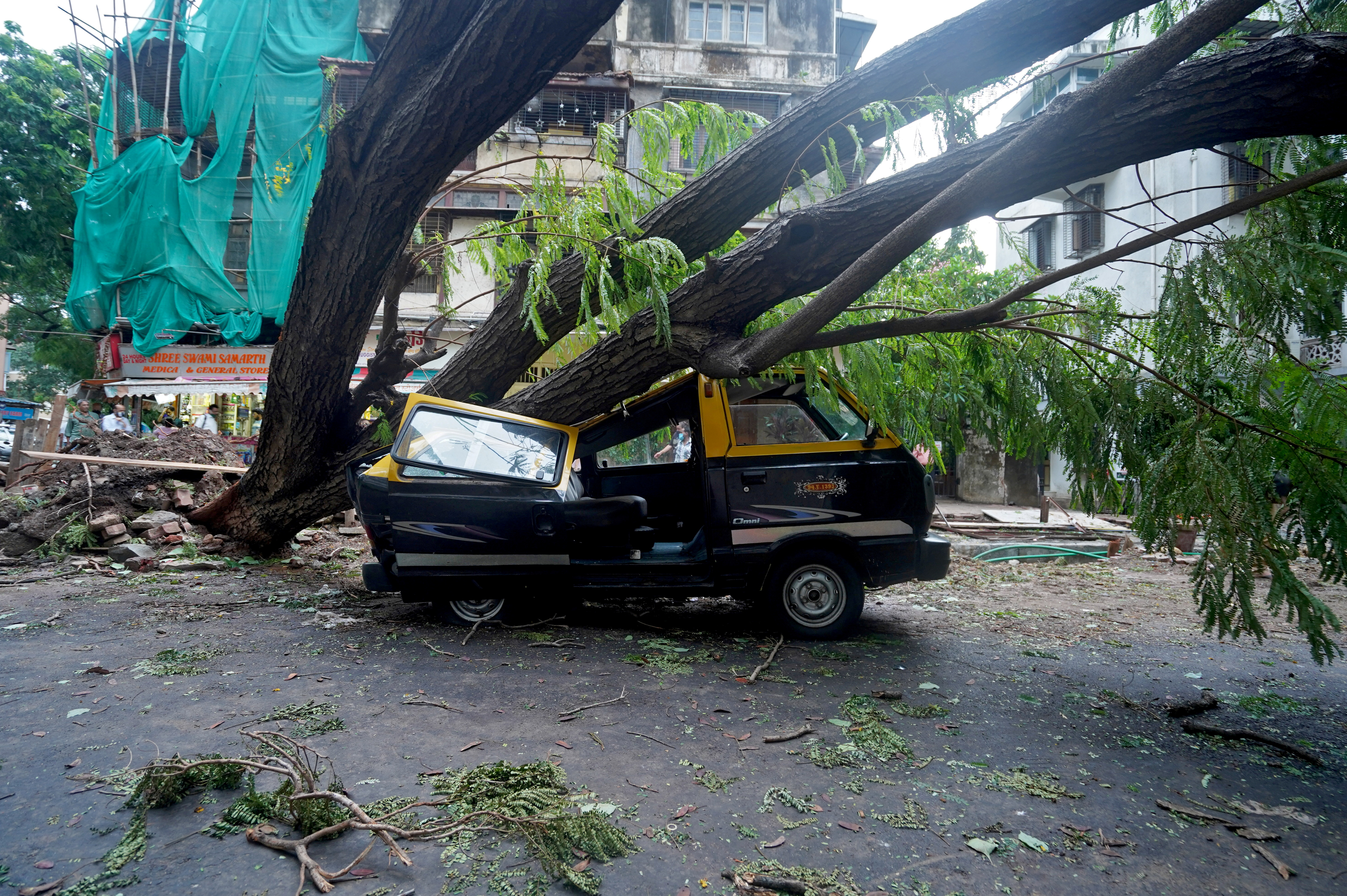 A damaged vehicle is seen under a fallen tree on a road after heavy winds caused by Cyclone Tauktae, in Mumbai, India, May 18, 2021. REUTERS/Hemanshi Kamani     TPX IMAGES OF THE DAY