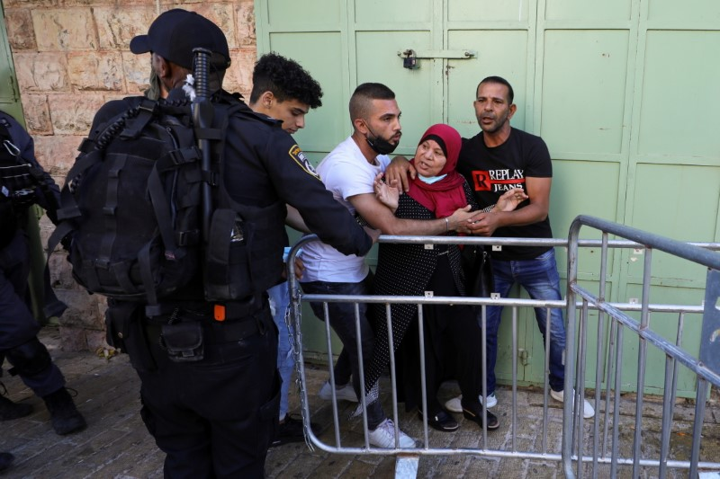 A Palestinian woman argues with Israeli police as she is evacuated amid tension ahead of a flag-waving procession by far-right youth, at Jerusalem's Old City, ?June 15, 2021. REUTERS/Ammar Awad