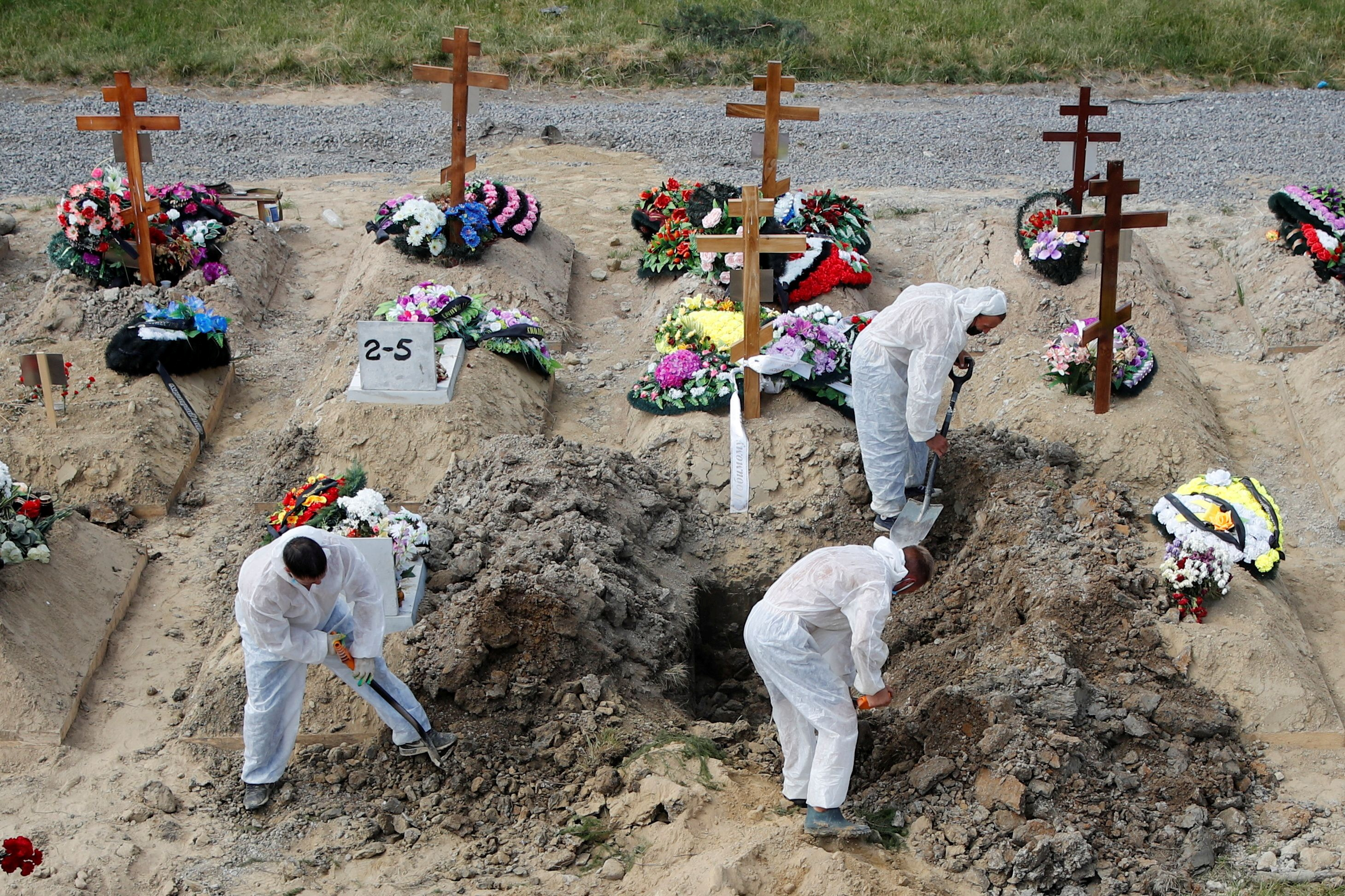 Grave diggers wearing personal protective equipment (PPE) as a preventive measure against the coronavirus disease (COVID-19) bury a person at a graveyard on the outskirts of Saint Petersburg, Russia June 25, 2021. REUTERS/Anton Vaganov