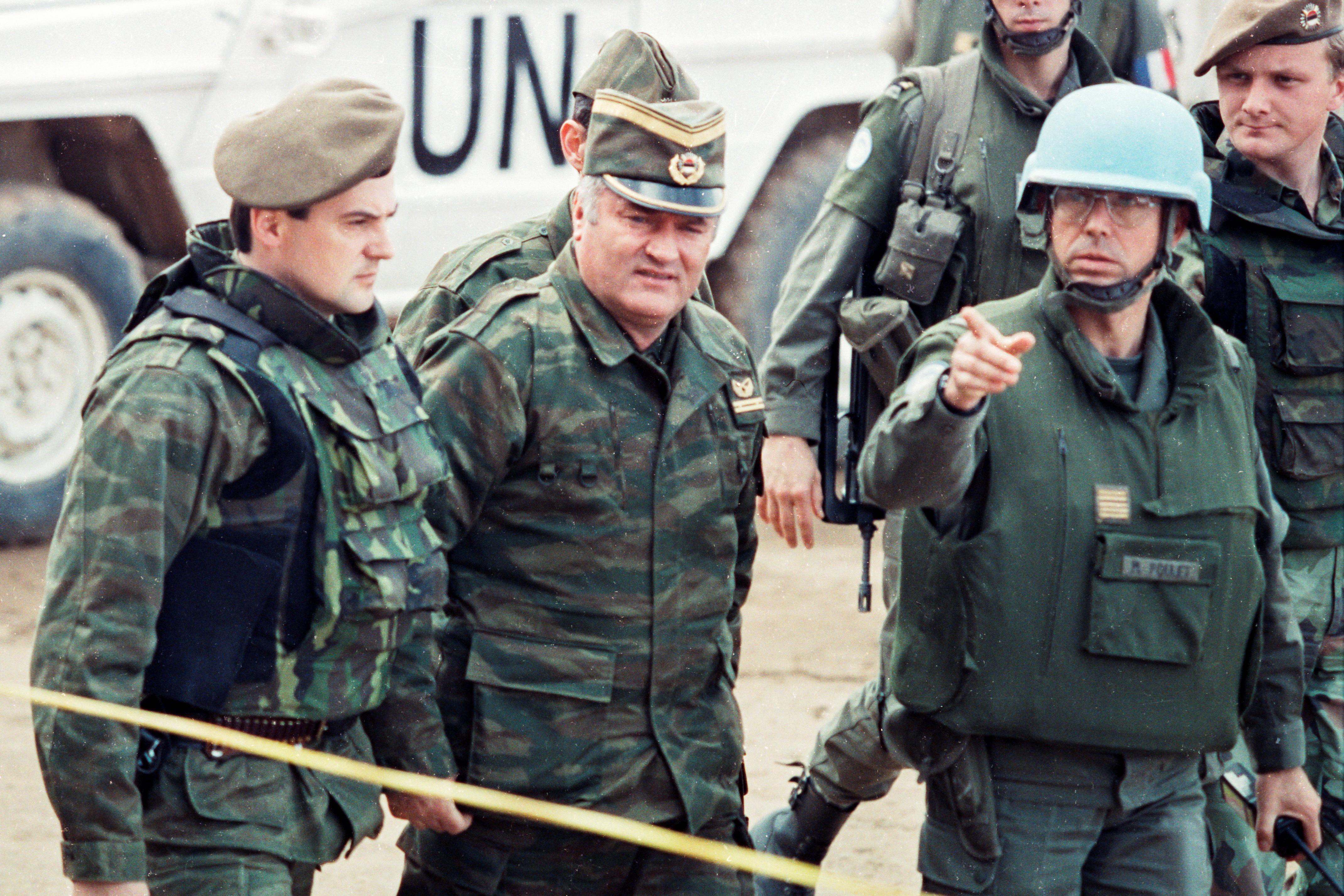 Генерал боснійських сербів Ратко Младич керується офіцером французького закордонного легіону, коли він прибуває на зустріч французького командувача ООН генералом Філіпом Морійоном в аеропорту Сараєво, Боснія і Герцеговина, в березні 1993 року. Знято в березні 1993 року. REUTERS / Кріс Хельгрен