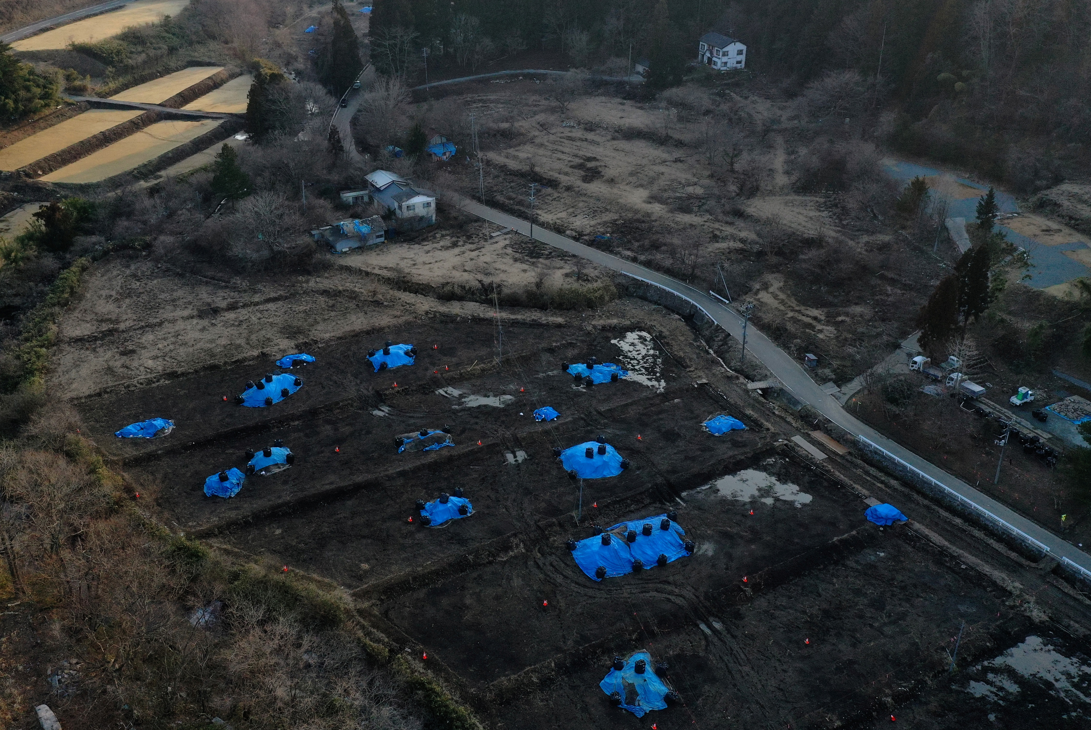 An aerial view shows Sakae Kato's house standing close to a field which is being decontaminated in a restricted zone in Namie, Fukushima Prefecture, Japan, February 21, 2021. Kato looks after 41 cats in his home and another empty building on his property. A decade ago, Kato stayed behind to rescue cats abandoned by neighbours who fled the radiation clouds belching from the nearby Fukushima nuclear plant. He won't leave.