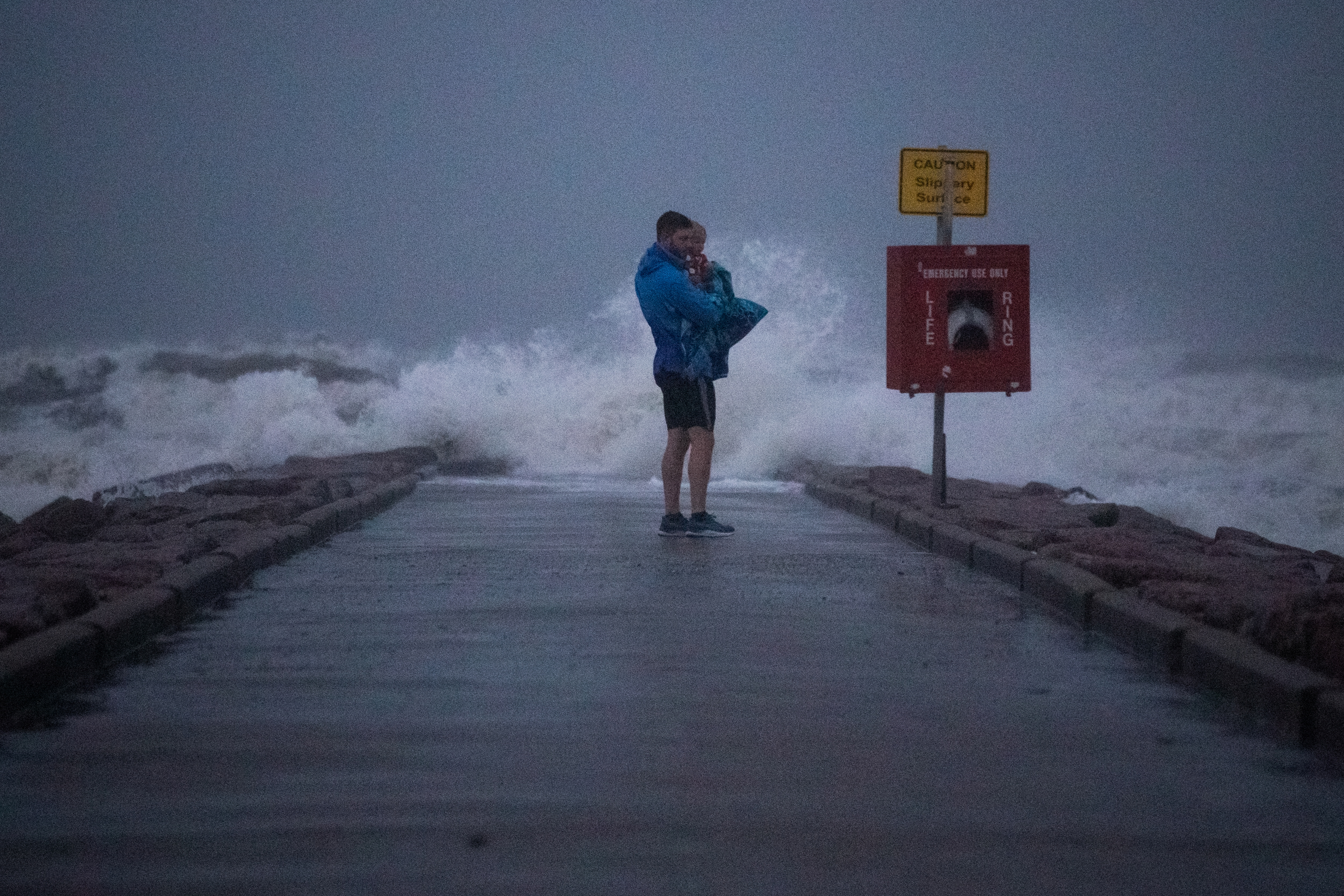 Local resident John Smith holds his 18-month-old son Owen as he stands near breaking waves on a pier ahead of the arrival of Tropical Storm Nicholas in Galveston, Texas, U.S., September 13, 2021. REUTERS/Adrees Latif