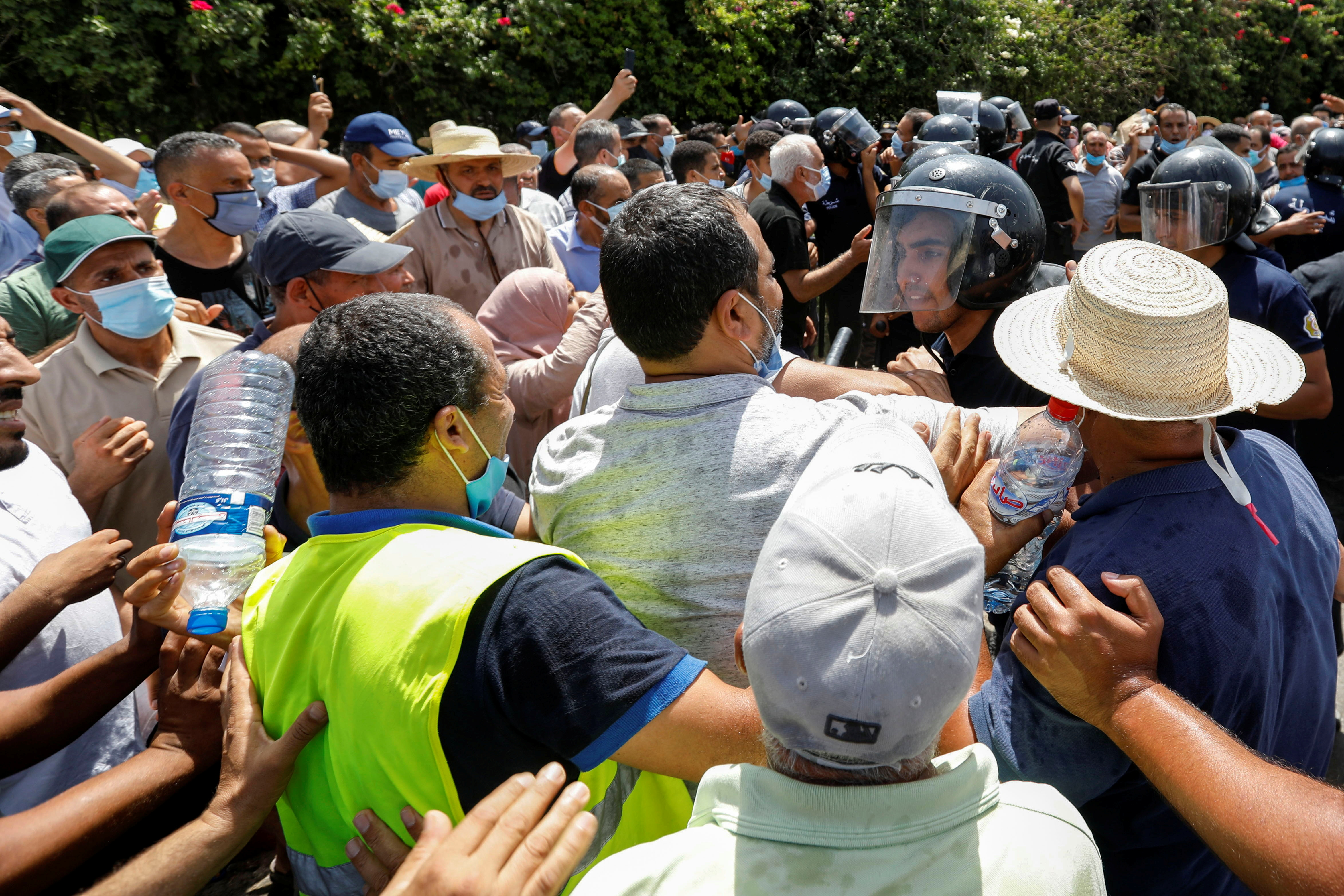 A police officer pushes back supporters of Tunisia's biggest political party, the moderate Islamist Ennahda, as they attempt to reach the parliament building in Tunis, Tunisia July 26, 2021. REUTERS/Zoubeir Souissi