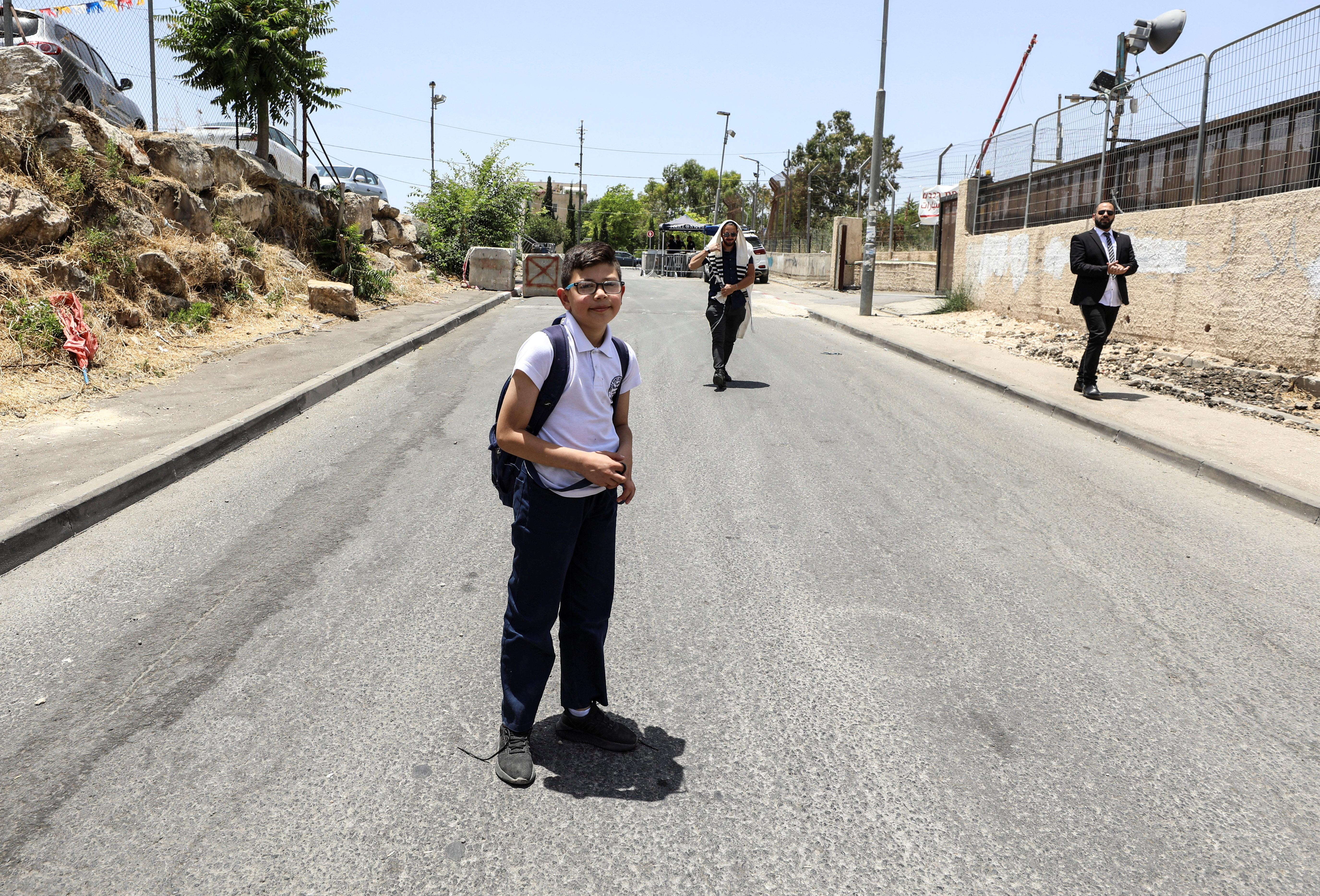 Ahmad, a member of the Abu Diab family, Palestinian residents of Sheikh Jarrah who face possible eviction after an Israeli court accepted Jewish settler land claims, stands in front of a Jewish man, as he makes his way home from school in his neighbourhood in East Jerusalem June 12, 2021. Picture taken June 12, 2021. REUTERS/Ammar Awad