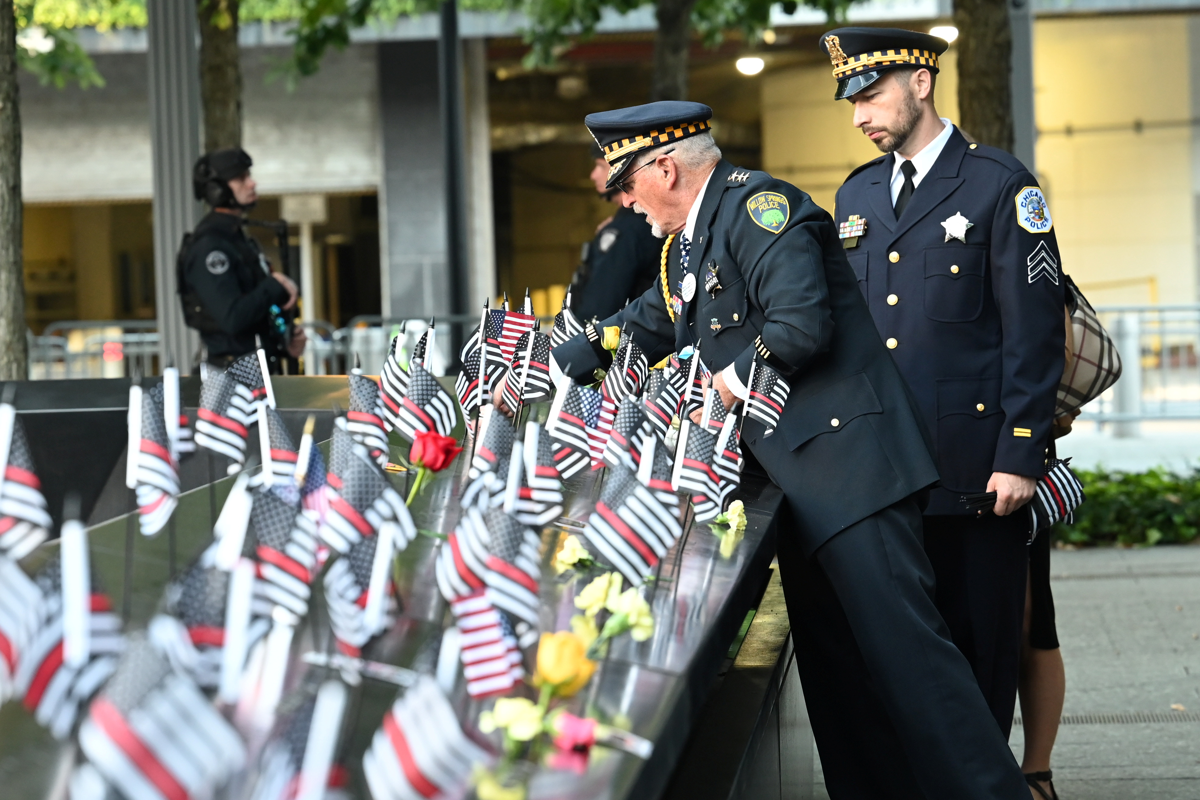 Retired Willow Springs, IL Chief Sam Pulia and his nephew, Chicago Police Sgt. Daniel Pulia place flags at the South Tower, before ceremonies marking the 20th anniversary of the September 11 attack, in New York, U.S., September 11, 2021. David Handschuh/Pool via REUTERS