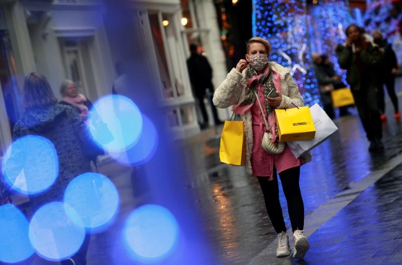 A shopper walks down the street in London, Britain December 18, 2020. REUTERS/Hannah Mckay