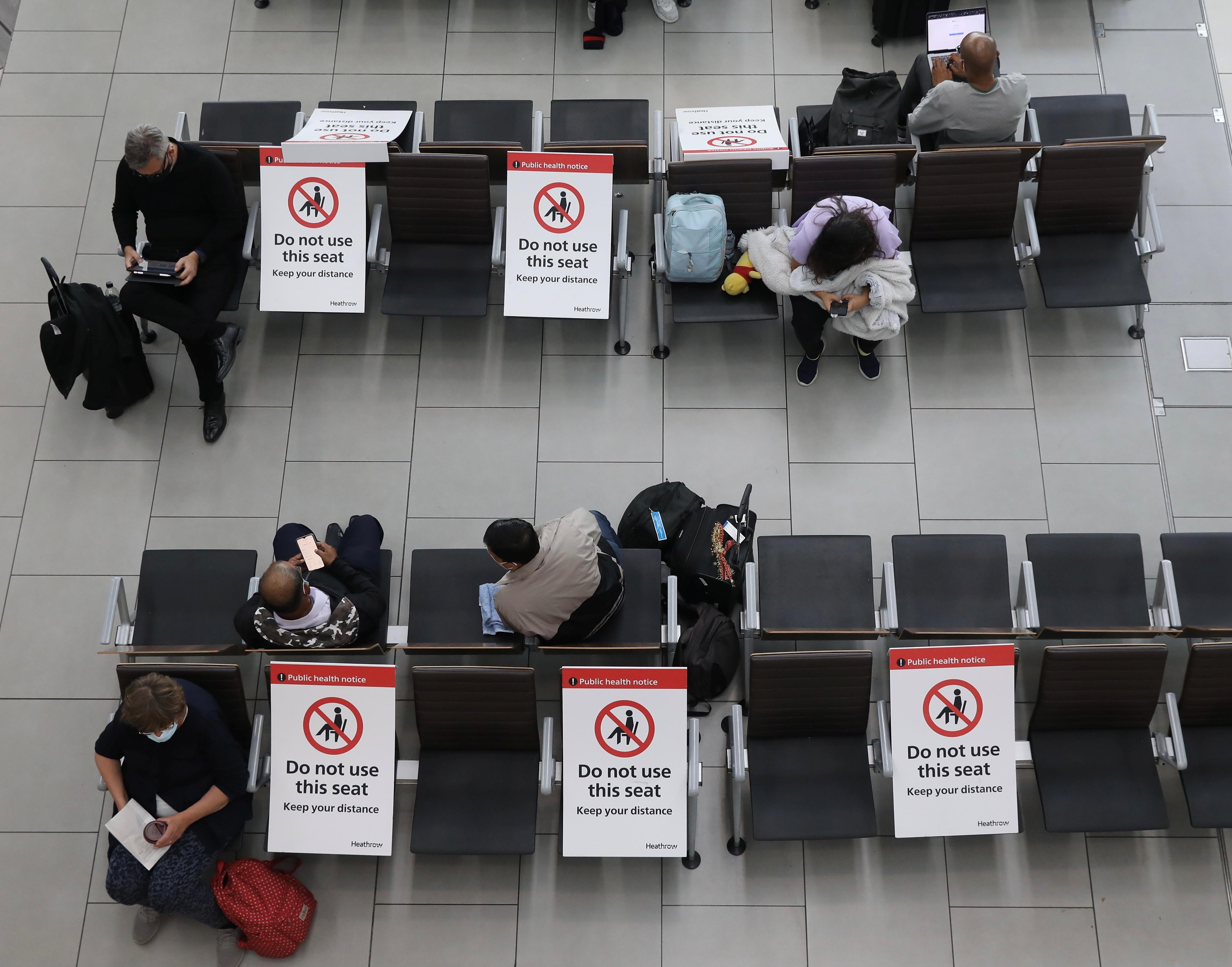 19 年 7 月 2021 日在英国伦敦发生冠状病毒病 (COVIDXNUMX) 大流行期间,乘客在希思罗机场等待社交距离较远的椅子。REUTERS/Kevin Coombs