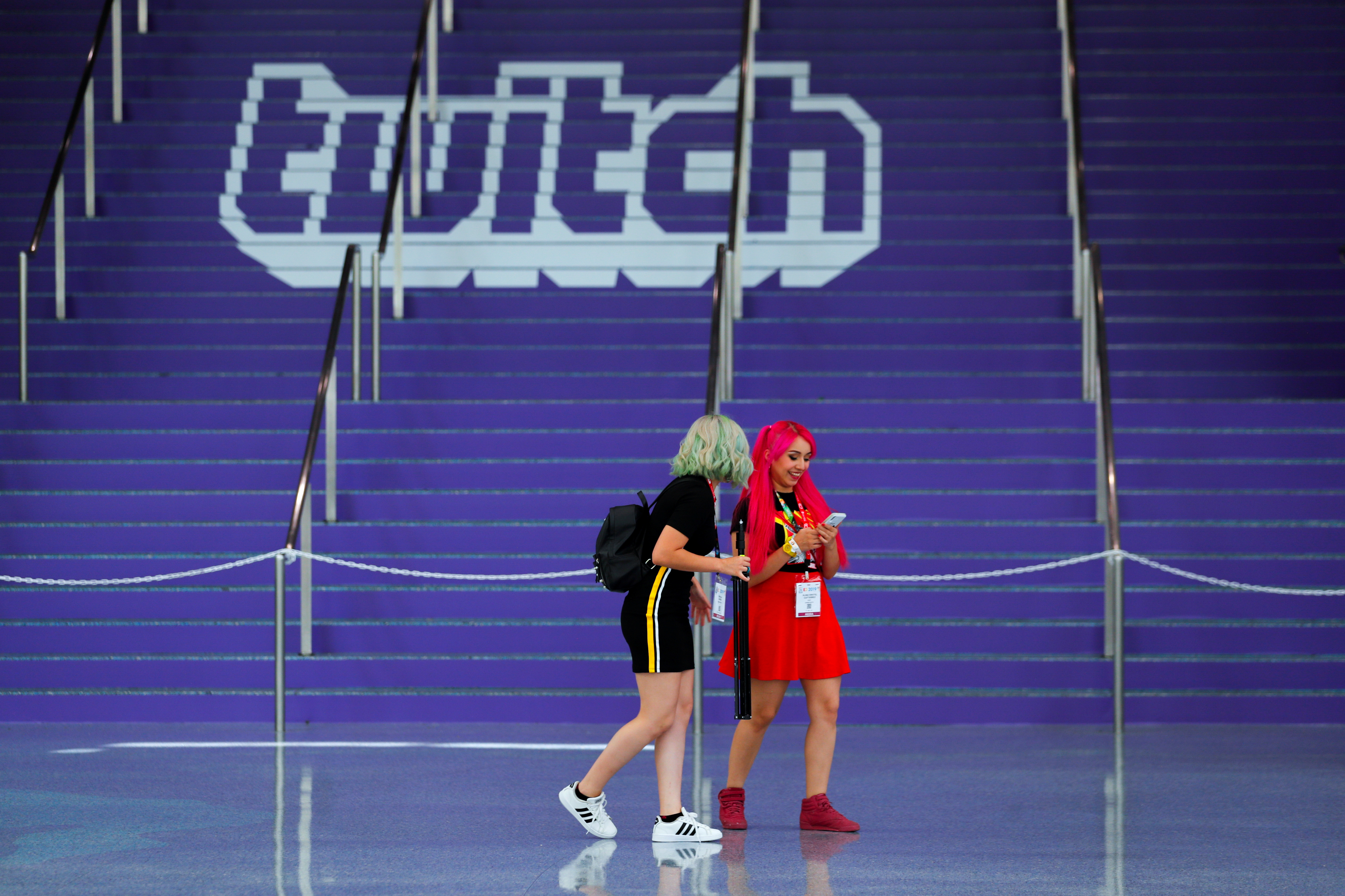 Attendees walk past a Twitch logo painted on stairs during opening day of E3, the annual video games expo revealing the latest in gaming software and hardware in Los Angeles, California, U.S., June 11, 2019.  REUTERS/Mike Blake