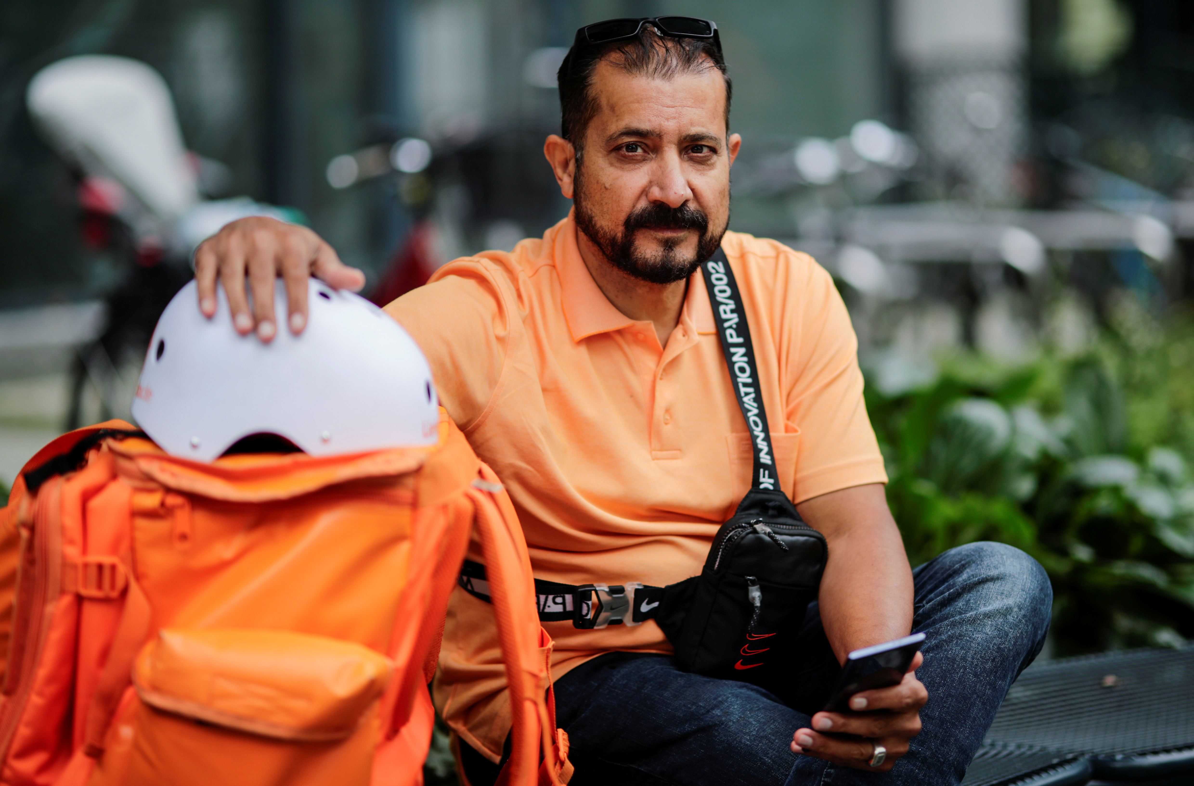Former Afghan Communication Minister Sayed Sadaat sits with his gear as he works for the food delivery service Lieferando in Leipzig, Germany, August 26, 2021. REUTERS/Hannibal Hanschke