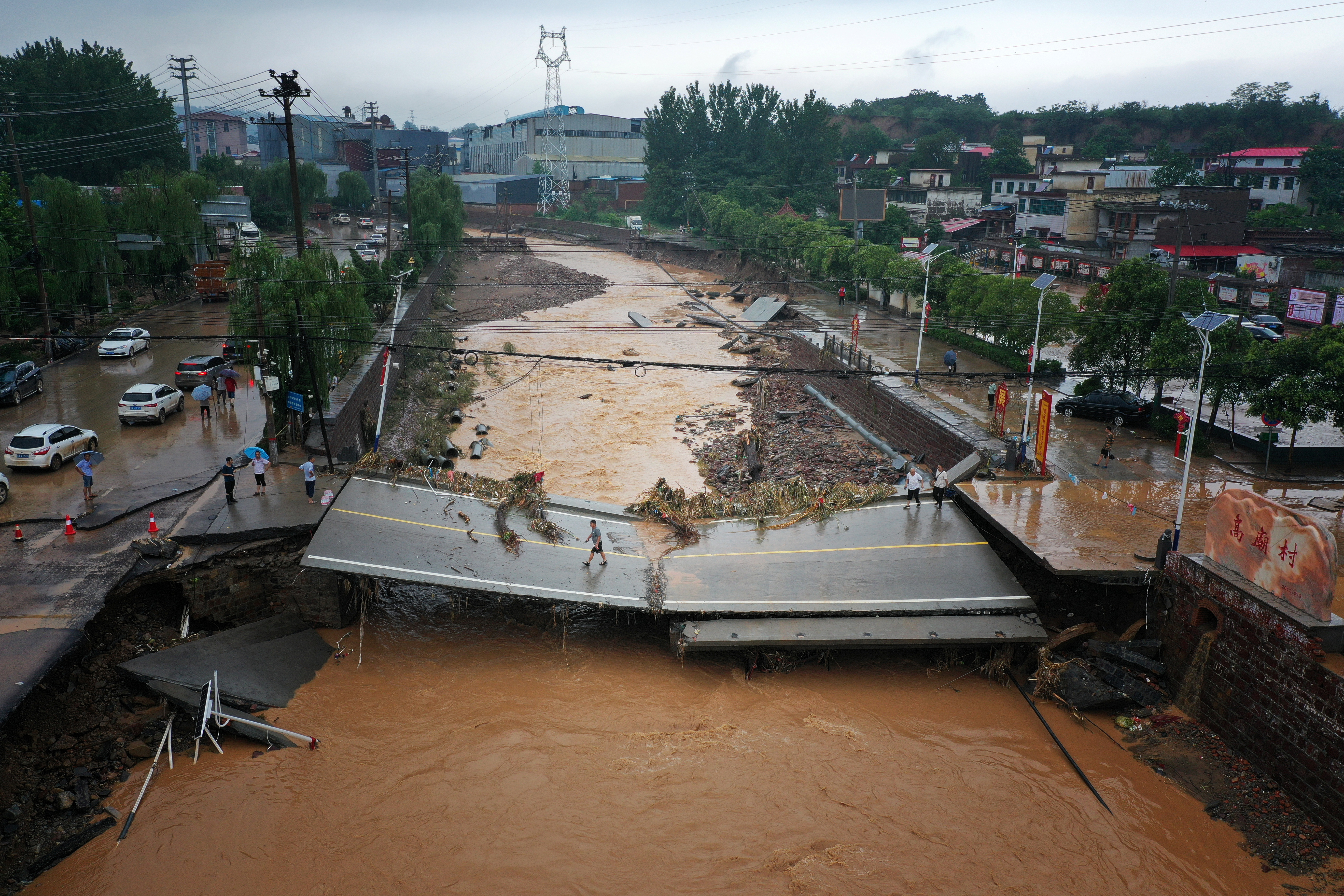 People walk on a damaged bridge after heavy rainfall flooded Gaomiao village of Gongyi in Henan province, China July 21, 2021. Picture taken July 21, 2021 with a drone. China Daily via REUTERS  ATTENTION EDITORS - THIS IMAGE WAS PROVIDED BY A THIRD PARTY. CHINA OUT.