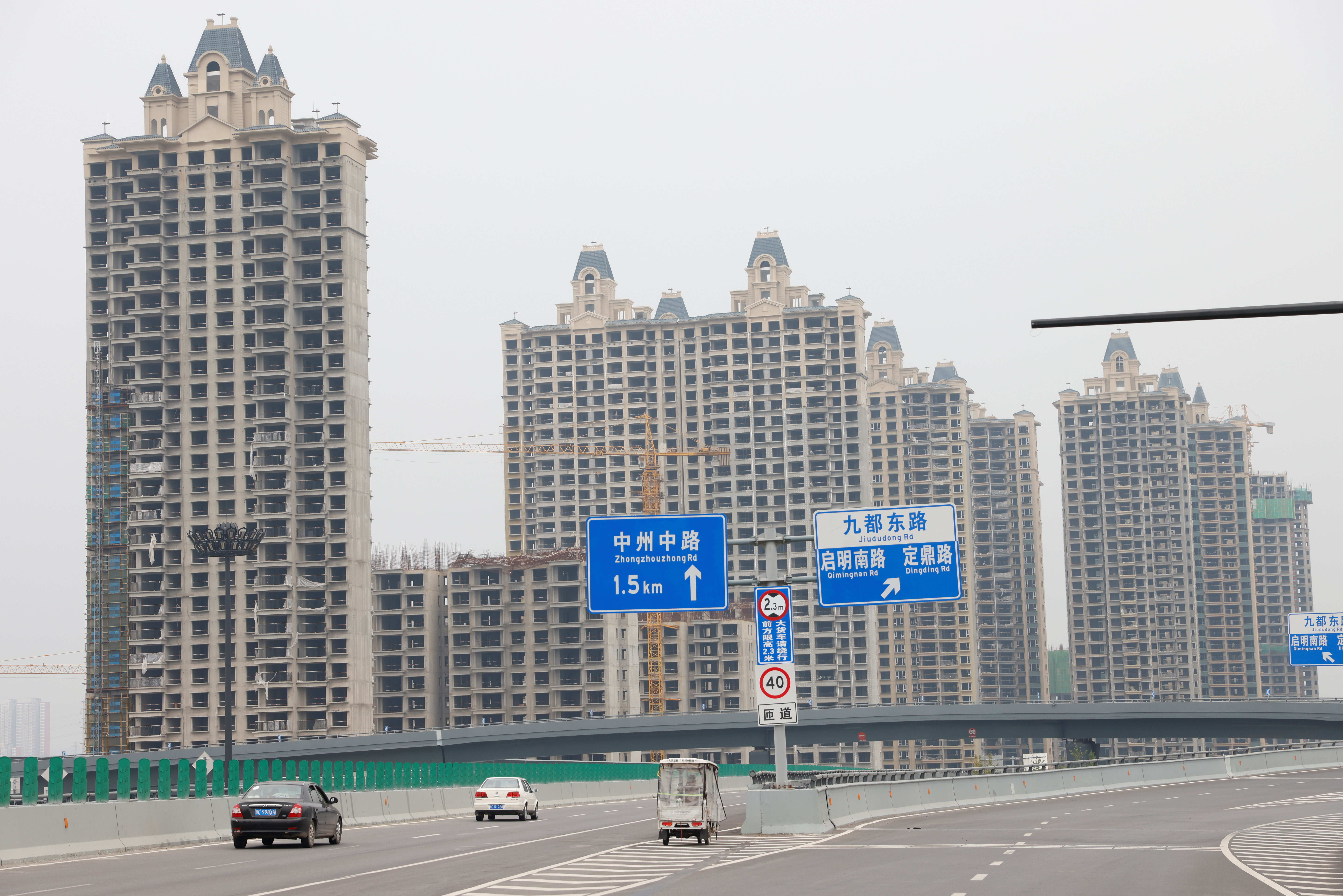 Vehicles drive by unfinished residential buildings from the Evergrande Oasis, a housing complex developed by Evergrande Group, in Luoyang, China September 16, 2021. Picture taken September 16, 2021. REUTERS/Carlos Garcia Rawlins