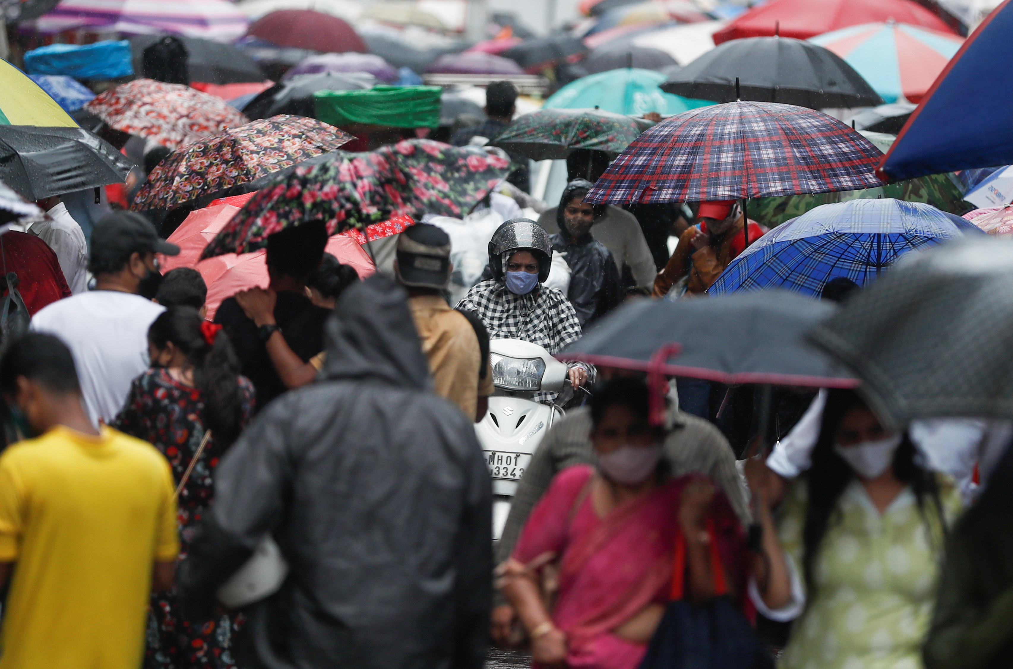 A woman rides a scooter through a crowded market on a rainy day amidst the spread of the coronavirus disease (COVID-19) in Mumbai, India, July 14, 2021. REUTERS/Francis Mascarenhas