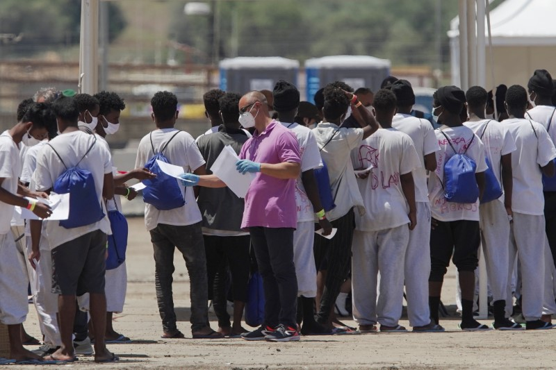 Migrants receive identity forms after disembarking 'Geo Barents', a ship run by Doctors Without Borders (MSF) that was given permission to dock at the Sicilian port of Augusta after a week of waiting at sea, before boarding the quarantine ship 'Aurelia', in Augusta, Italy, June 18, 2021. REUTERS/Antonio Parrinello