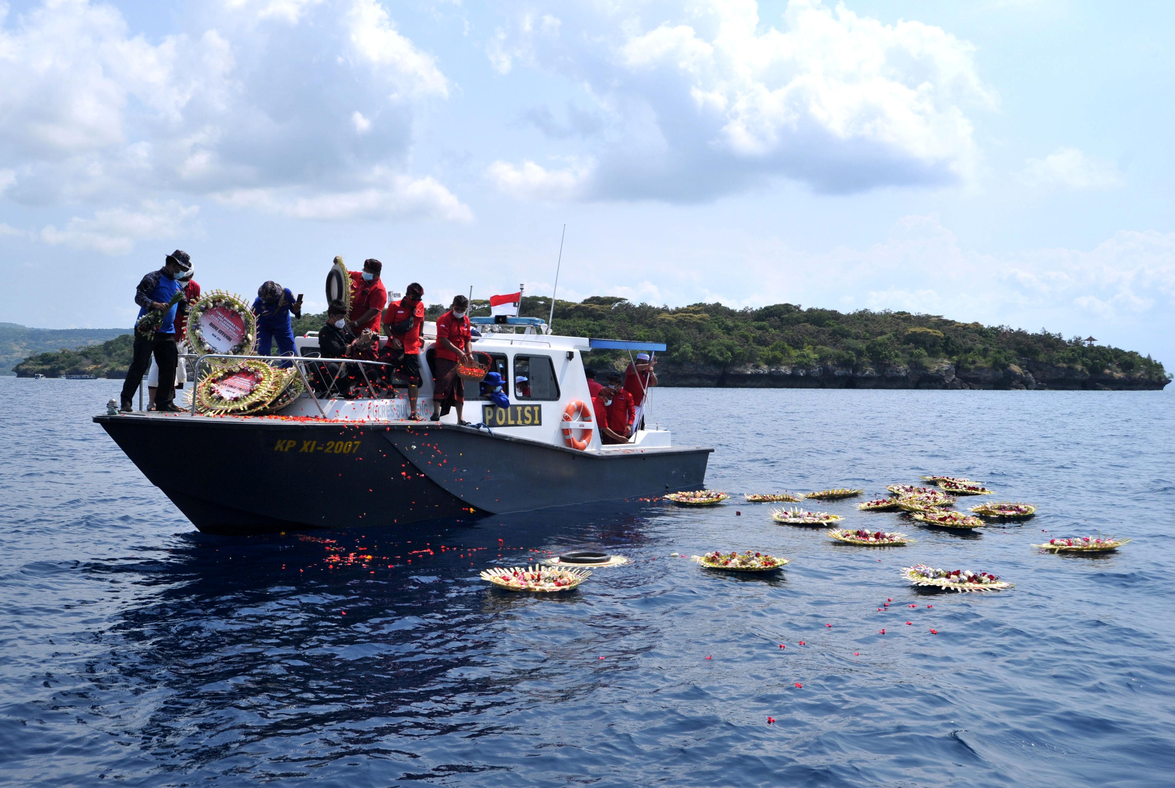 Orangorang melempar bunga dan kelopak dengan nama awak kapal selam KRI Nanggala402 yang tenggelam dari kapal saat berdoa di laut dekat Labuhan Lalang, Bali, Indonesia 26 April 2021, dalam foto ini diambil oleh Antara Foto/Fikri Yusuf/via Reuters