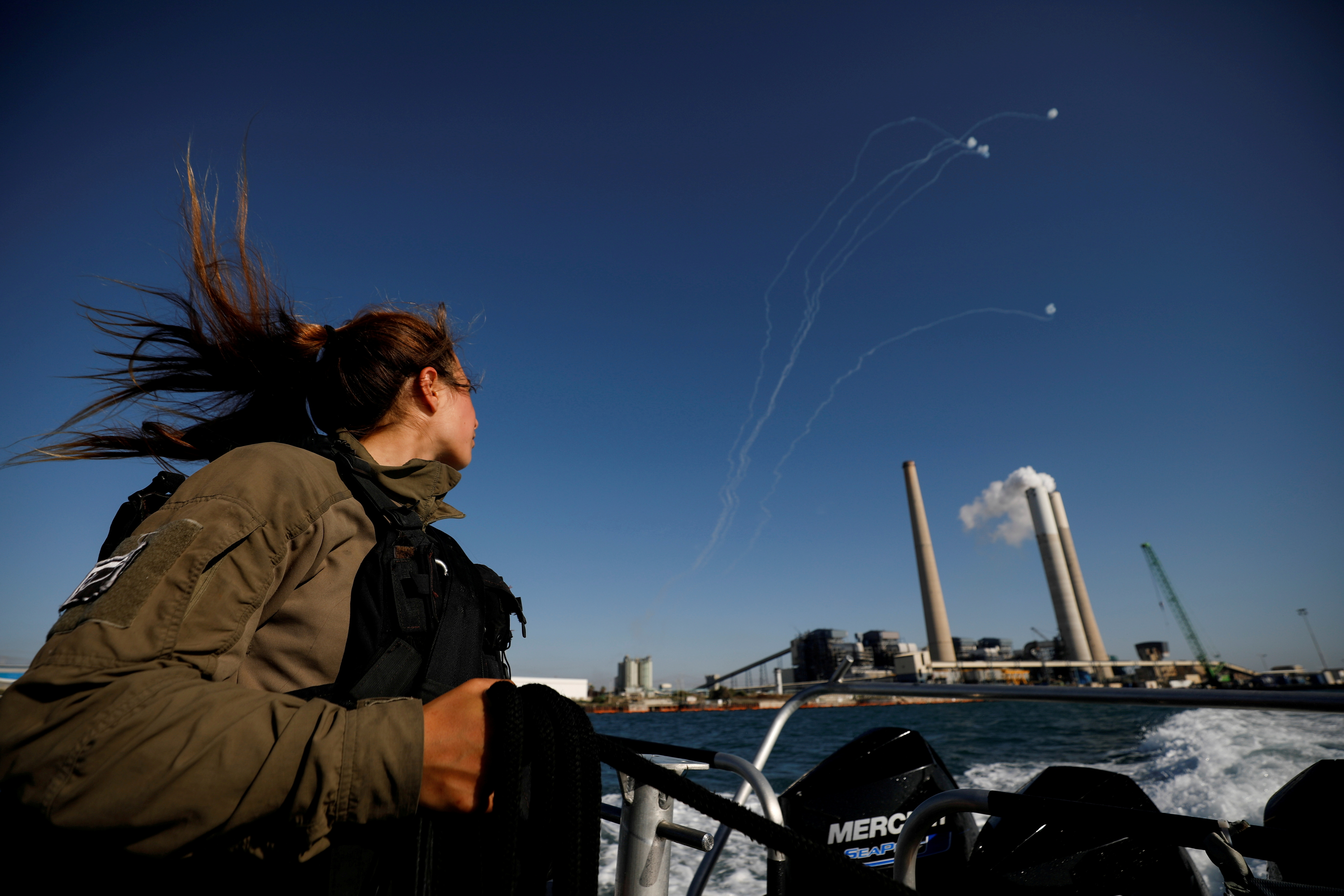An Israeli soldier looks on as Israel's Iron Dome anti-missile system intercept rockets launched from the Gaza Strip towards Israel, as it seen from a naval boat patrolling the Mediterranean Sea off the southern Israeli coast as Israel-Gaza fighting rages on May 19, 2021 REUTERS/ Amir Cohen