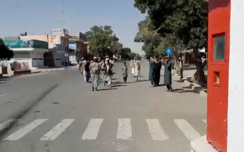 People gather on the street as Taliban fighters stand guard on main road intersection in city of Ghazni, Afghanistan in this screen grab taken from a video released by the Taliban on August 12, 2021. Taliban Handout/via REUTERS
