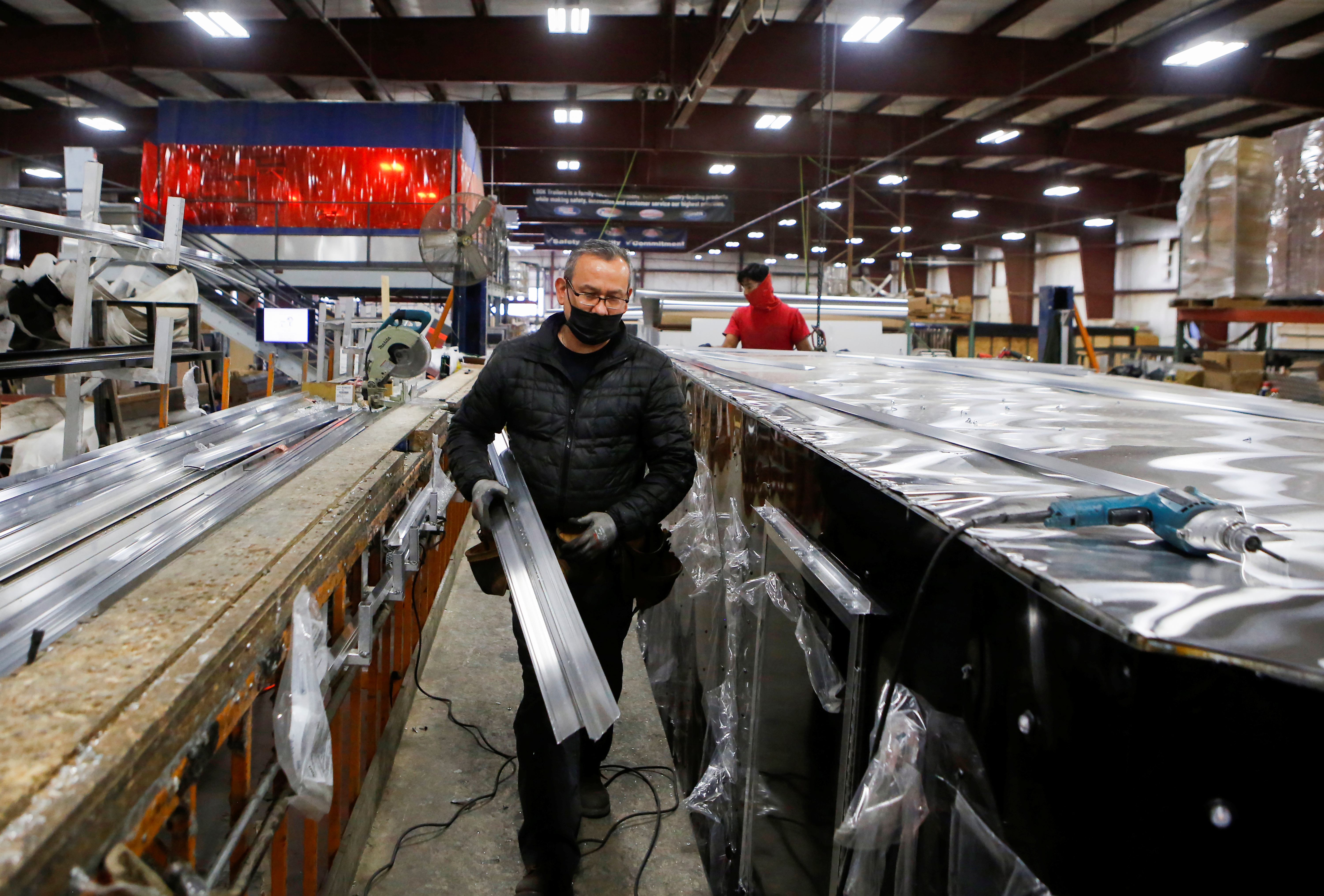 Carlos Hernandez and Hector Torres install an aluminium roof at Look Trailers cargo trailer manufacturing facility in Middlebury, Indiana, U.S., April 1, 2021.  REUTERS/Eileen T. Meslar