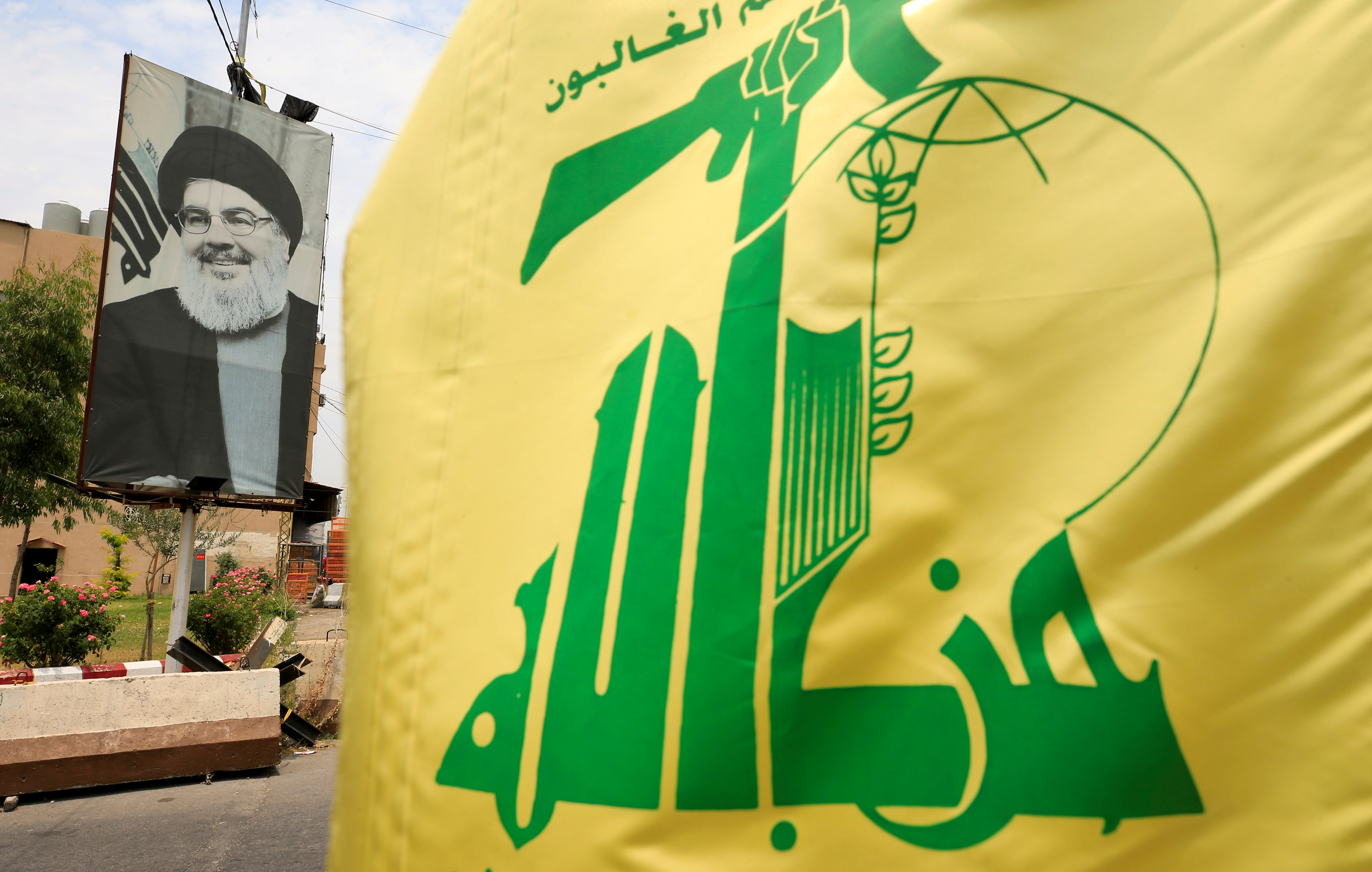 A Hezbollah flag and a poster depicting Lebanon's Hezbollah leader Sayyed Hassan Nasrallah are pictured along a street, near Sidon, Lebanon July 7, 2020. REUTERS/Ali Hashisho/File Photo