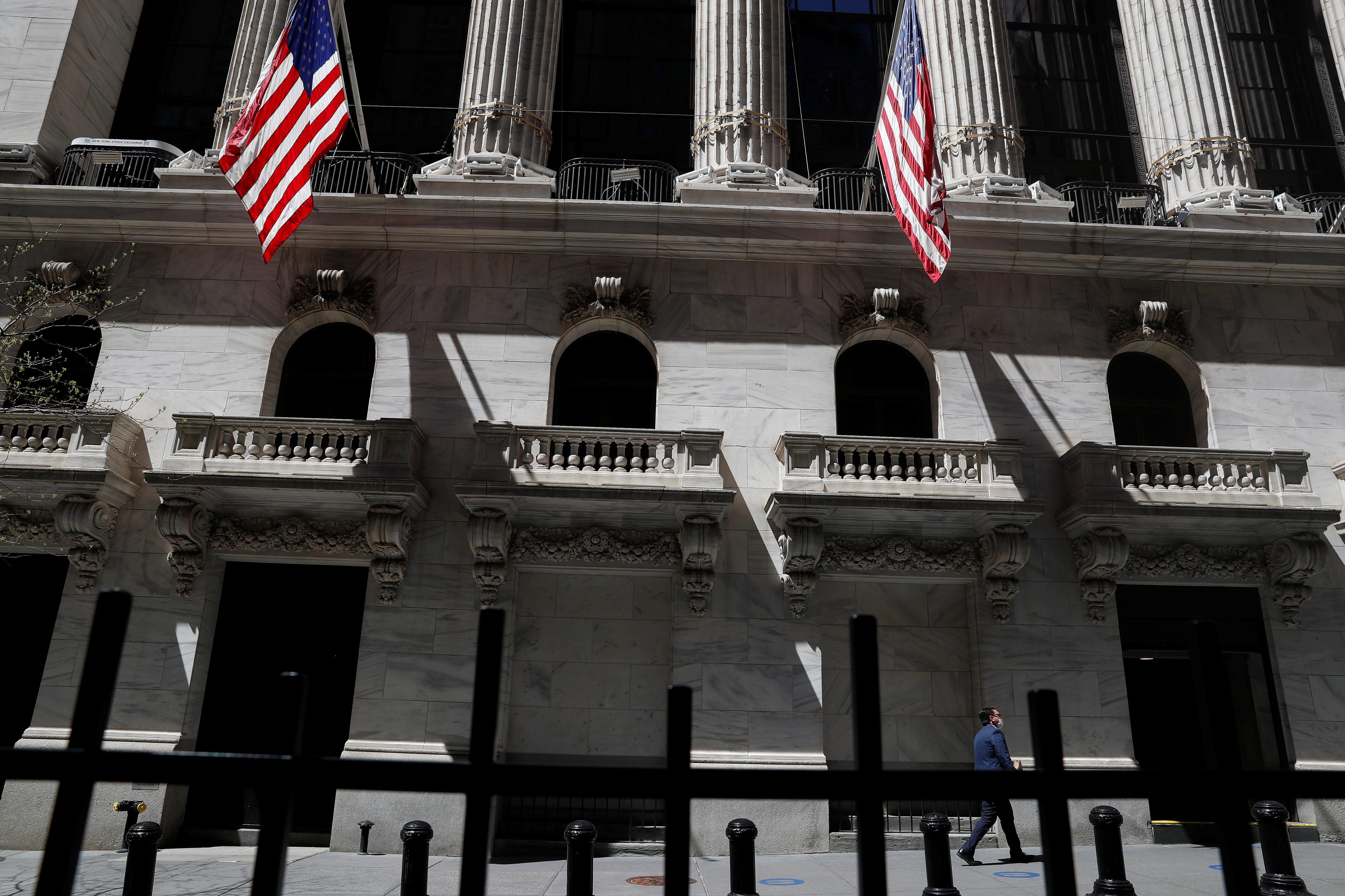 A trader walks outside the New York Stock Exchange in New York City, U.S., April 26, 2021. REUTERS/Shannon Stapleton