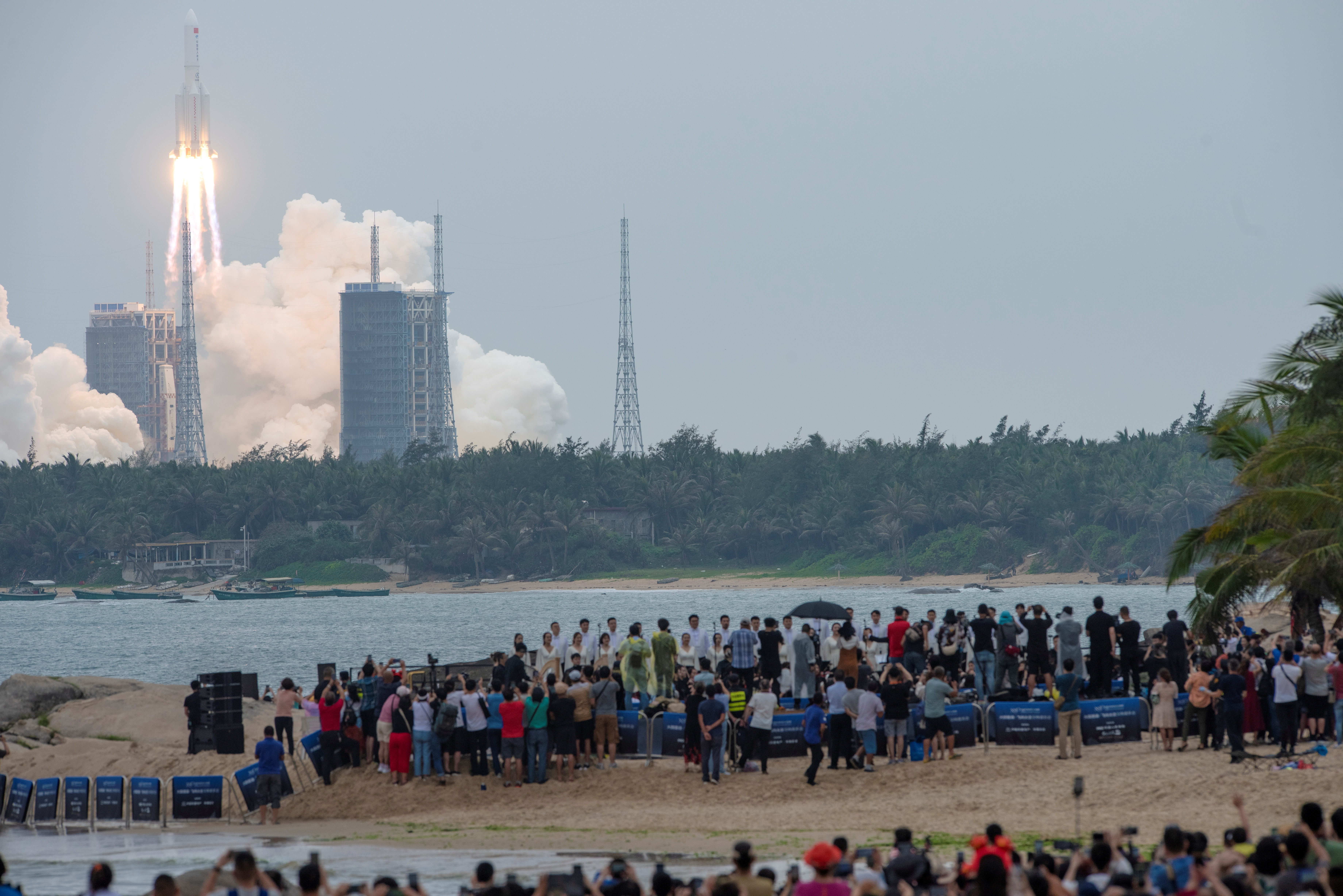 People watch from a beach as the Long March-5B Y2 rocket, carrying the core module of China's space station Tianhe, takes off from Wenchang Space Launch Center in Hainan province, China April 29, 2021. China Daily via REUTERS