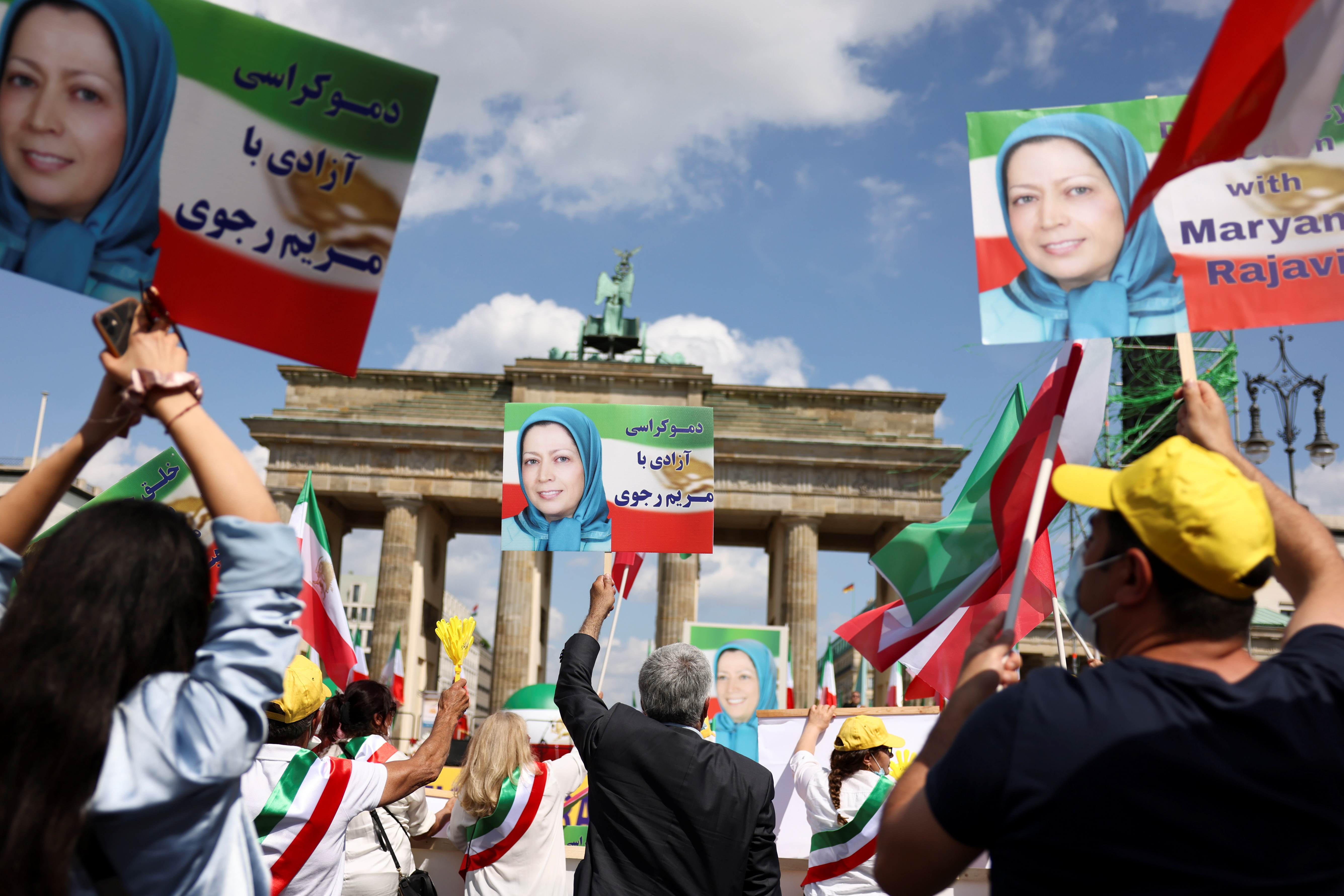 Supporters of the National Council of Resistance of Iran (NCRI) hold protraits of Iranian opposition leader Maryam Rajavi during a protest against the government in Teheran and the use of the death penalty in Iran, in front of the Brandenburg Gate in Berlin, Germany, July 10, 2021. REUTERS/Christian Mang
