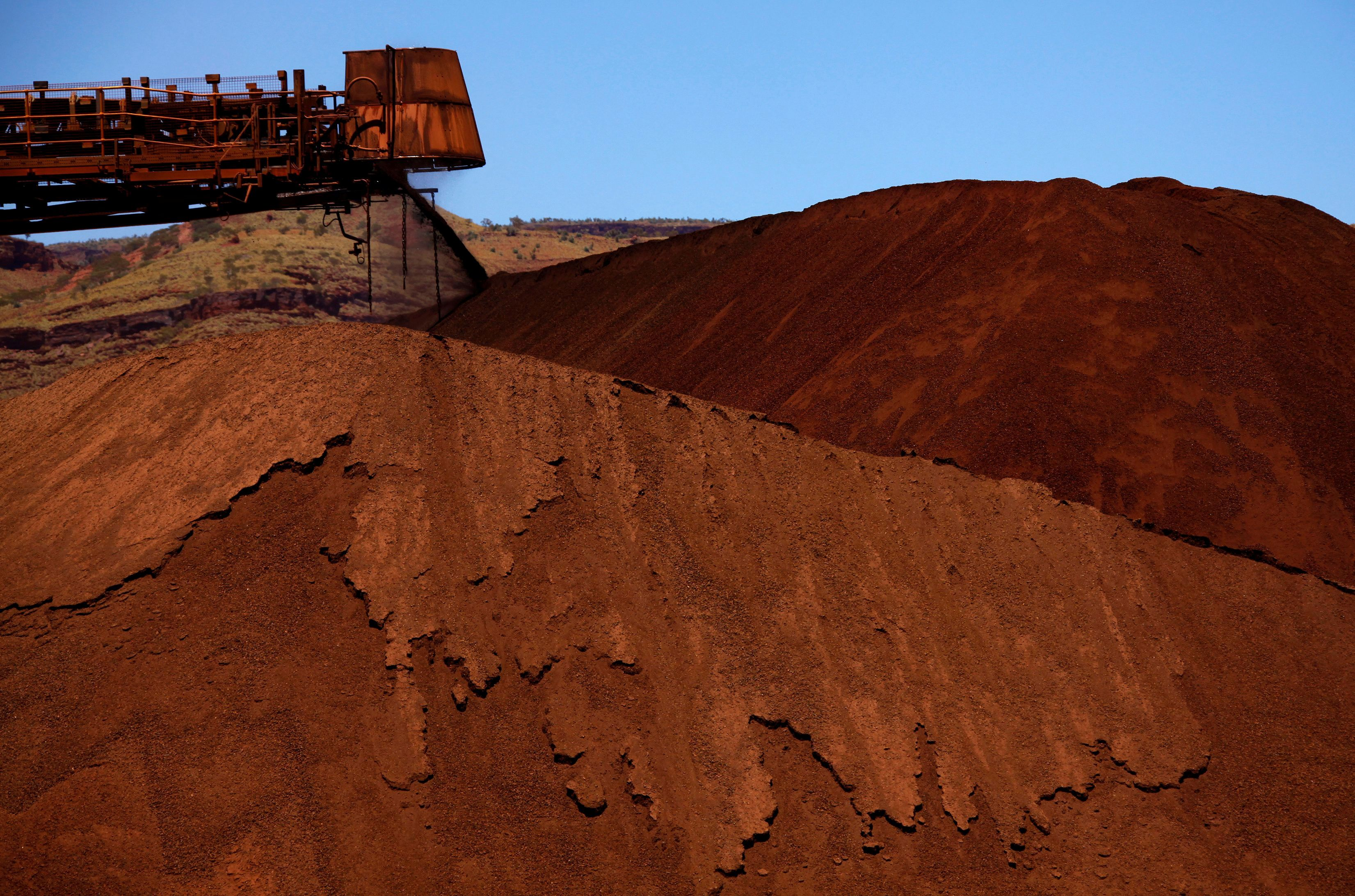 A stacker unloads iron ore onto a pile at a mine located in the Pilbara region of Western Australia December 2, 2013. REUTERS/David Gray/File Photo