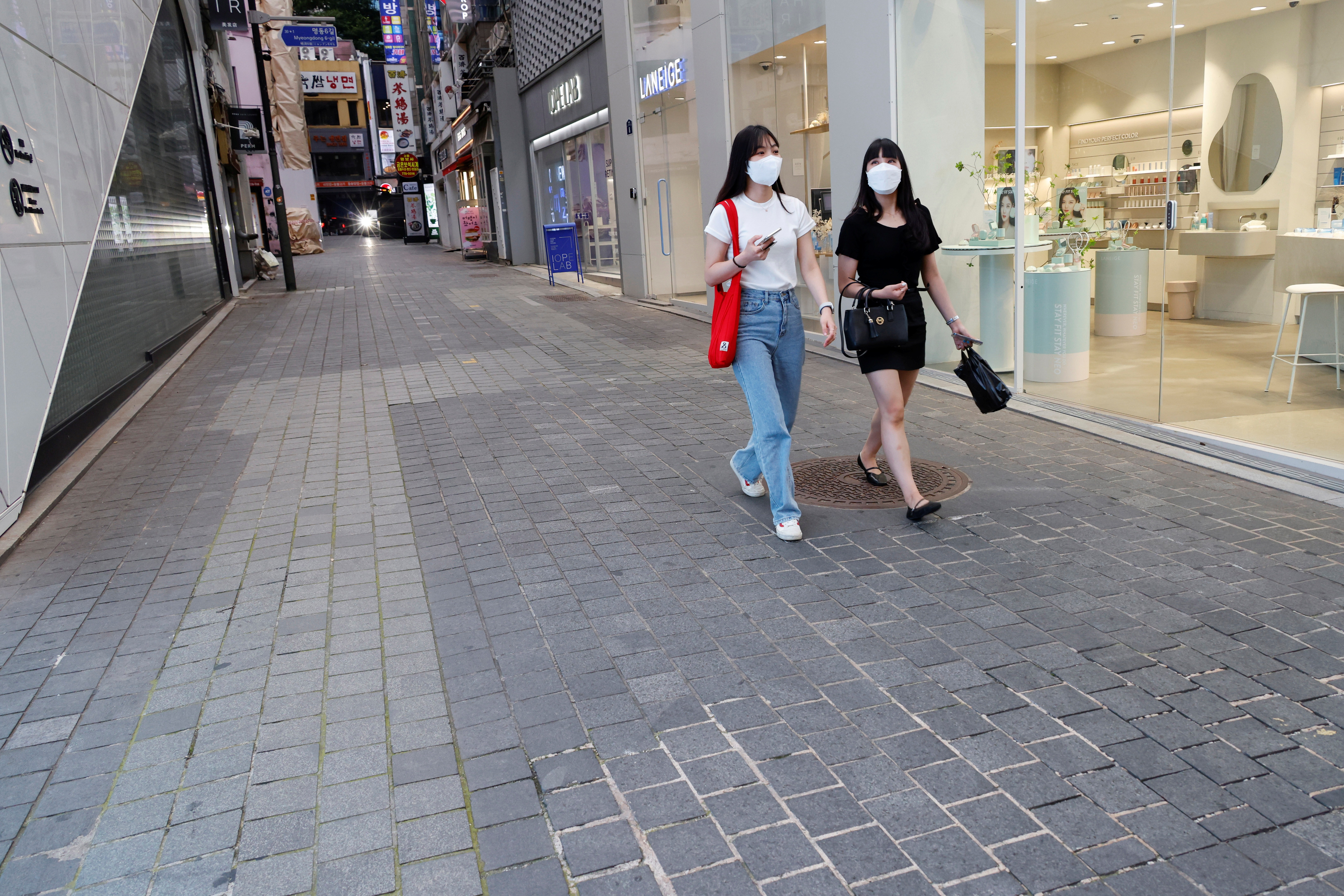 Women walk on an empty street amid tightened social distancing rules due to the coronavirus disease (COVID-19) pandemic in Seoul, South Korea, July 12, 2021. REUTERS/Heo Ran