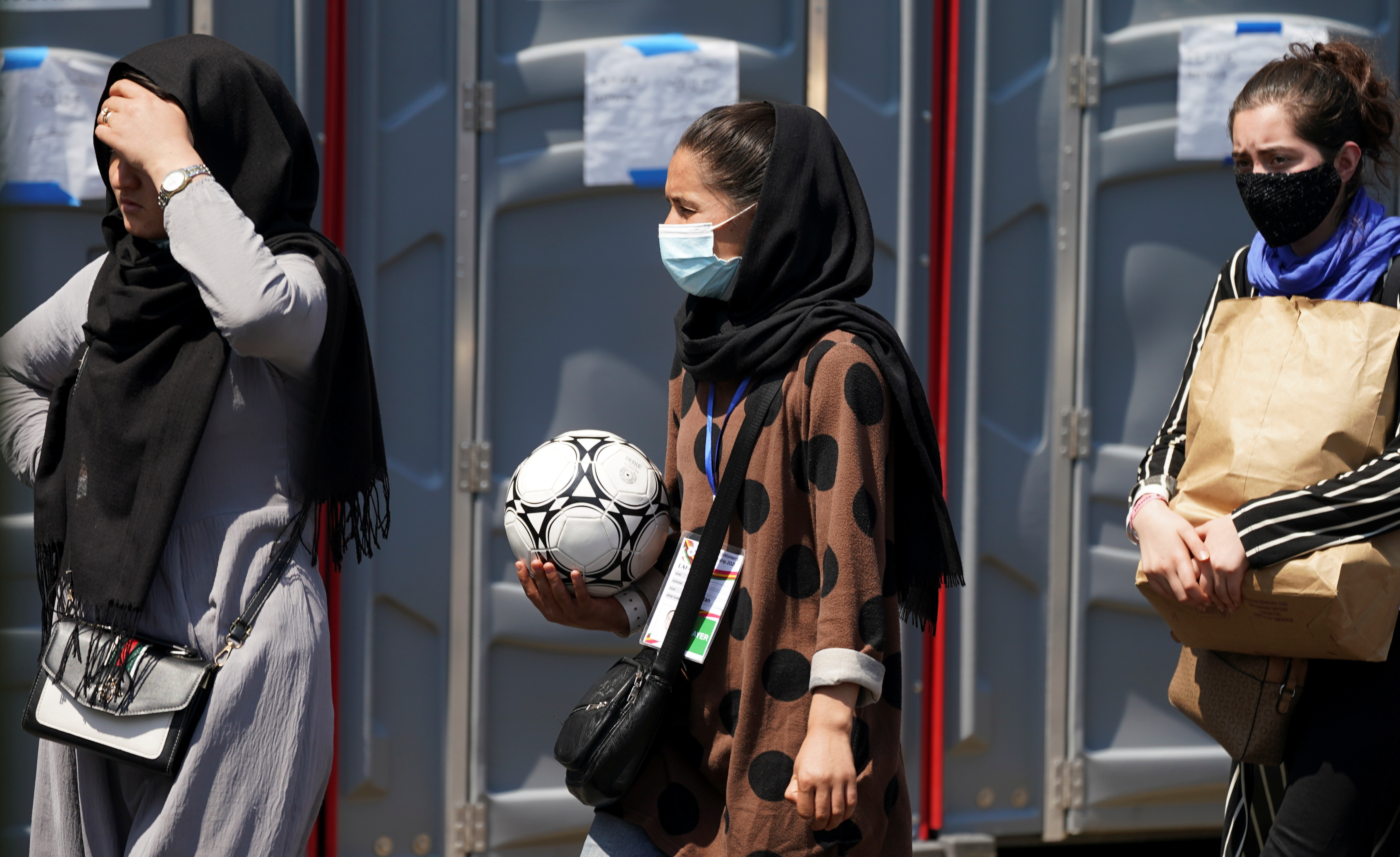 An Afghan woman holding a soccer ball and wearing a CAFA (Central Asian Football Association) credential, waits in line at a processing center for refugees evacuated from Afghanistan at the Dulles Expo Center near Dulles International Airport in Chantilly, Virginia, U.S., August 24, 2021. REUTERS/Kevin Lamarque/File Photo