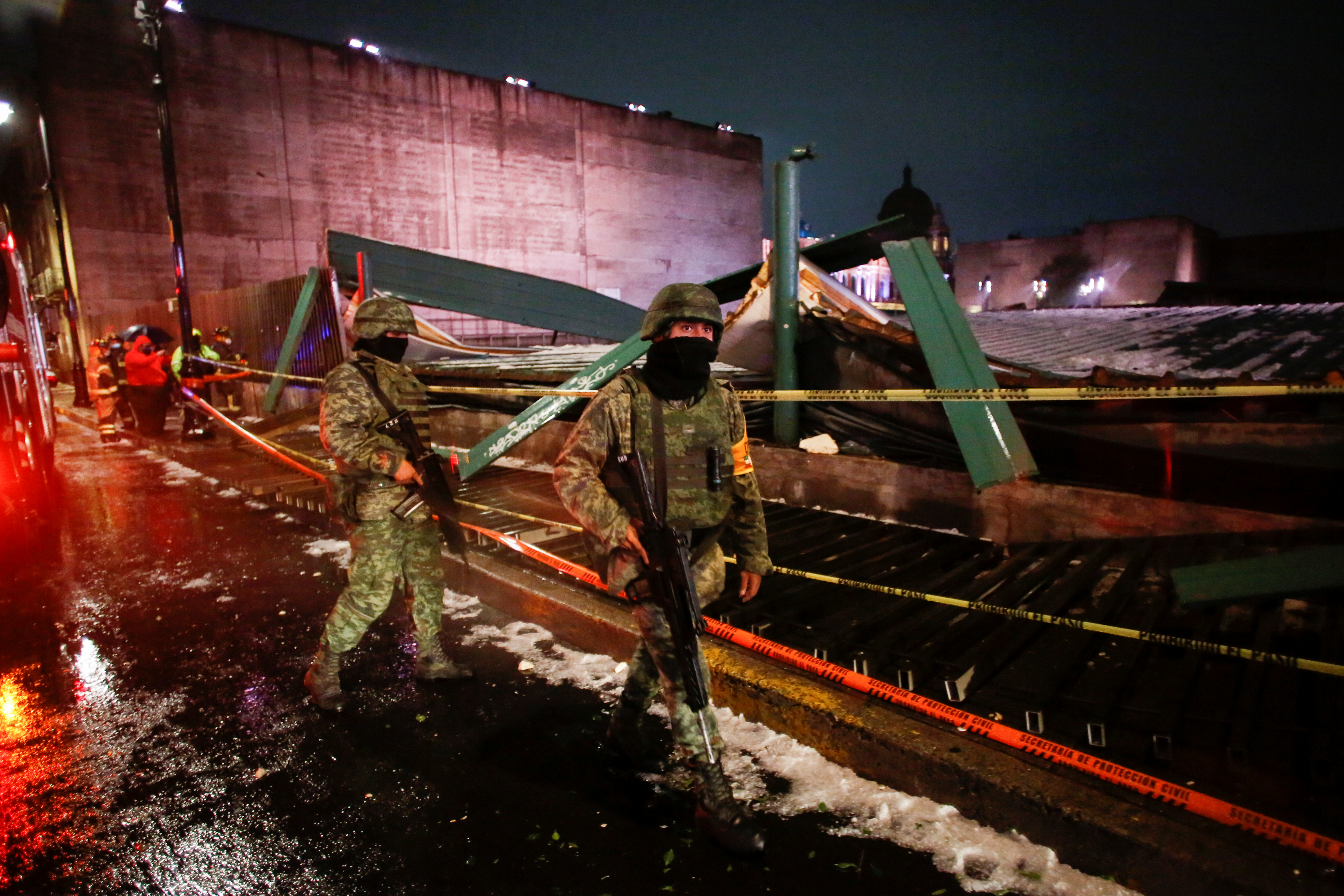 Soldiers walk by a scene where the roof protecting the