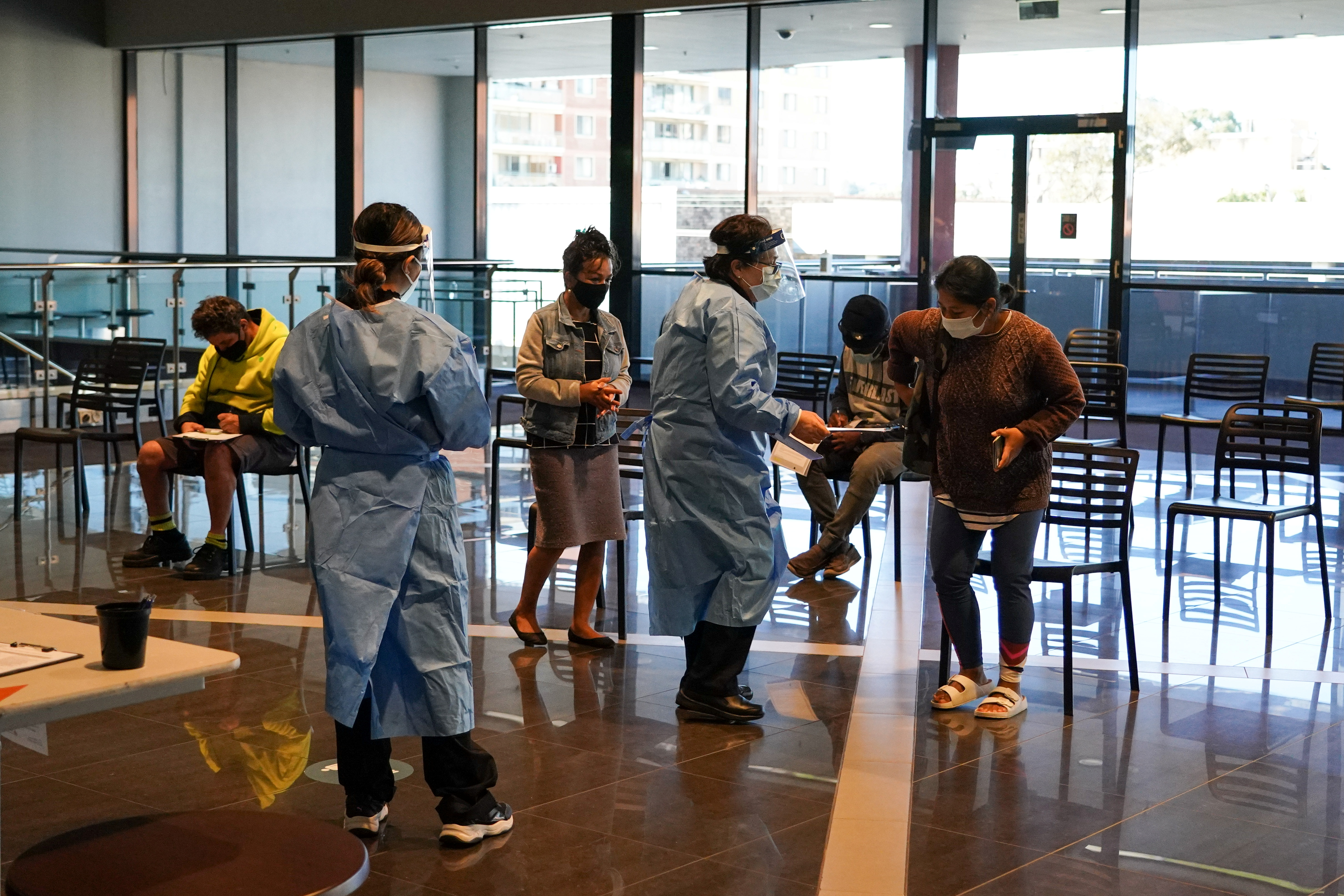Medical staff assist members of the public in the waiting area at a coronavirus disease (COVID-19) vaccination clinic at the Bankstown Sports Club as the city experiences an extended lockdown, in Sydney, Australia, August 3, 2021. REUTERS/Loren Elliott