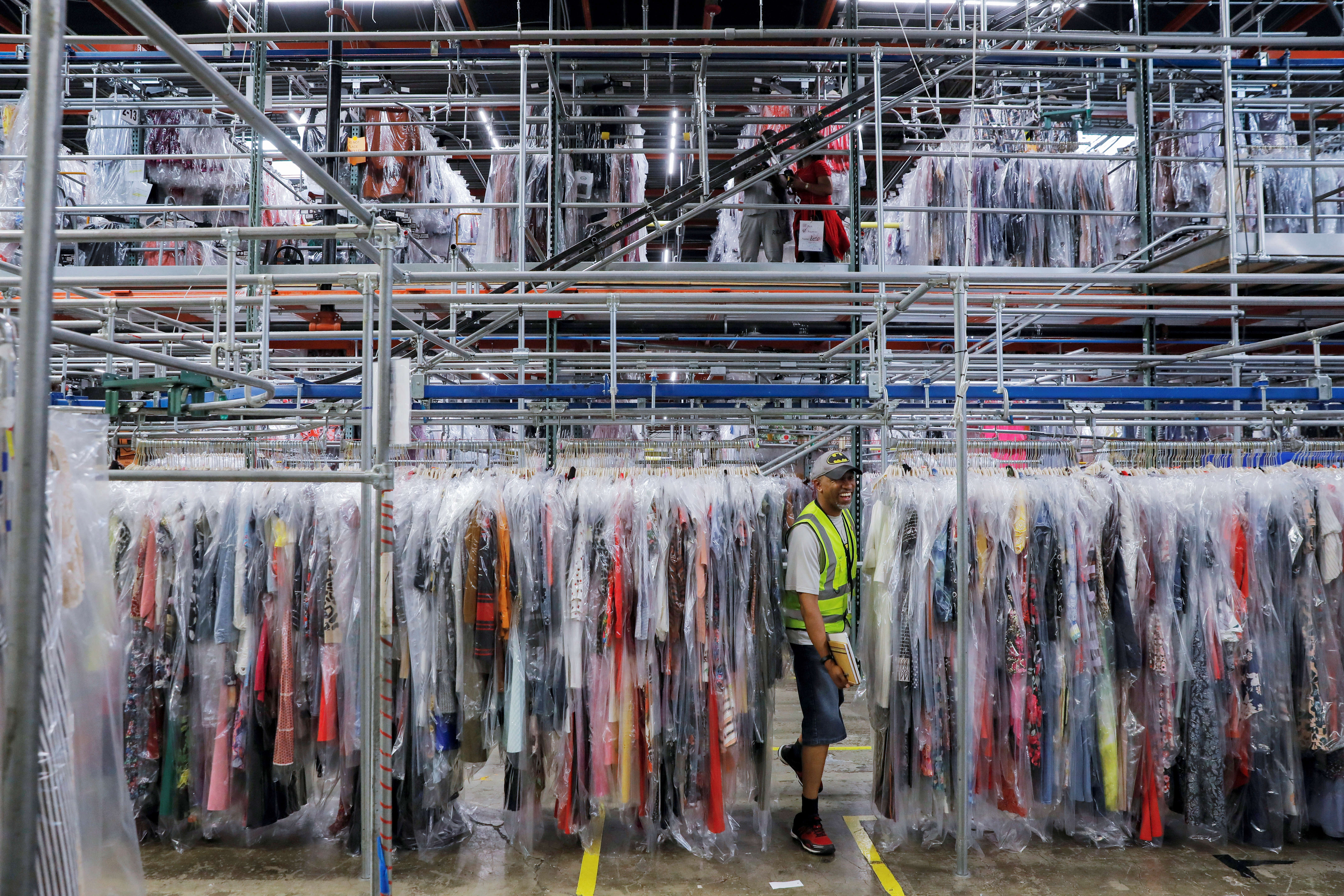 A person moves through clothing in the storage area at Rent the Runway's