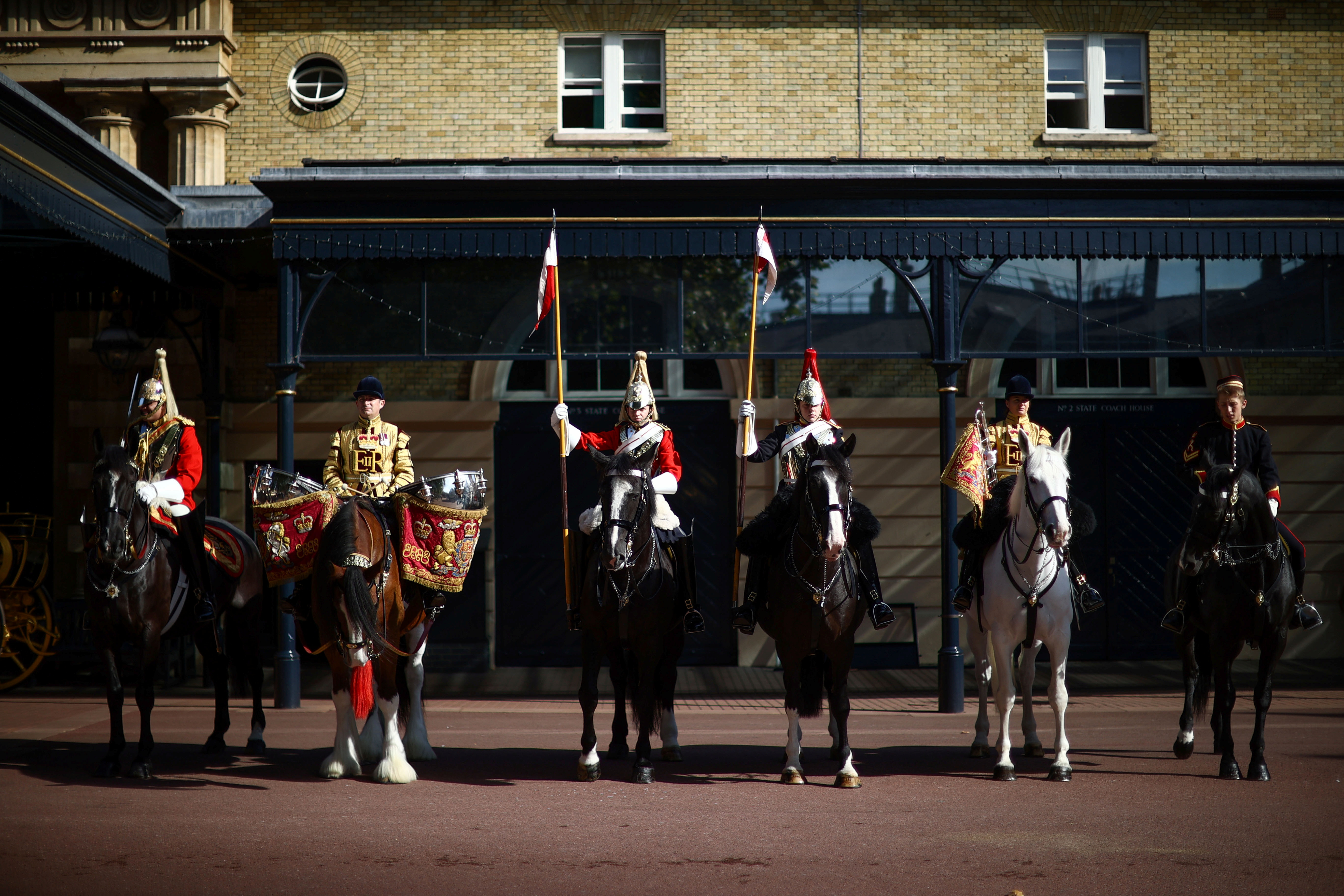 Members of the Household Cavalry ride on horses in the courtyard of the Royal Mews during the media launch of the 'Platinum Jubilee Celebration: A Gallop Through History' at Buckingham Palace in London, Britain, September 21, 2021. REUTERS/Hannah McKay