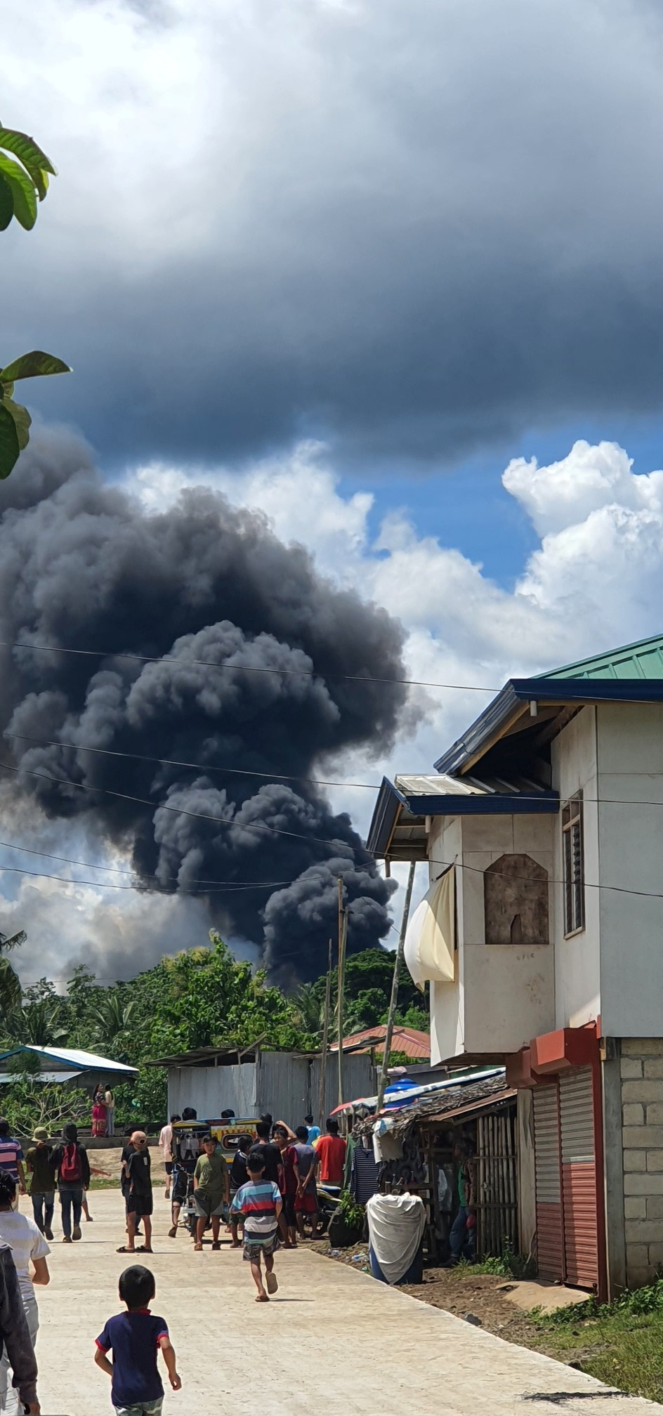 Residents gather as smoke rises from the wreckage, after a Philippines Air Force Lockheed C-130 transport plane, carrying troops, crashed on landing in Jolo, Sulu, Philippines July 4, 2021 in this image obtained from social media. Bogs Muhajiran via REUTERS