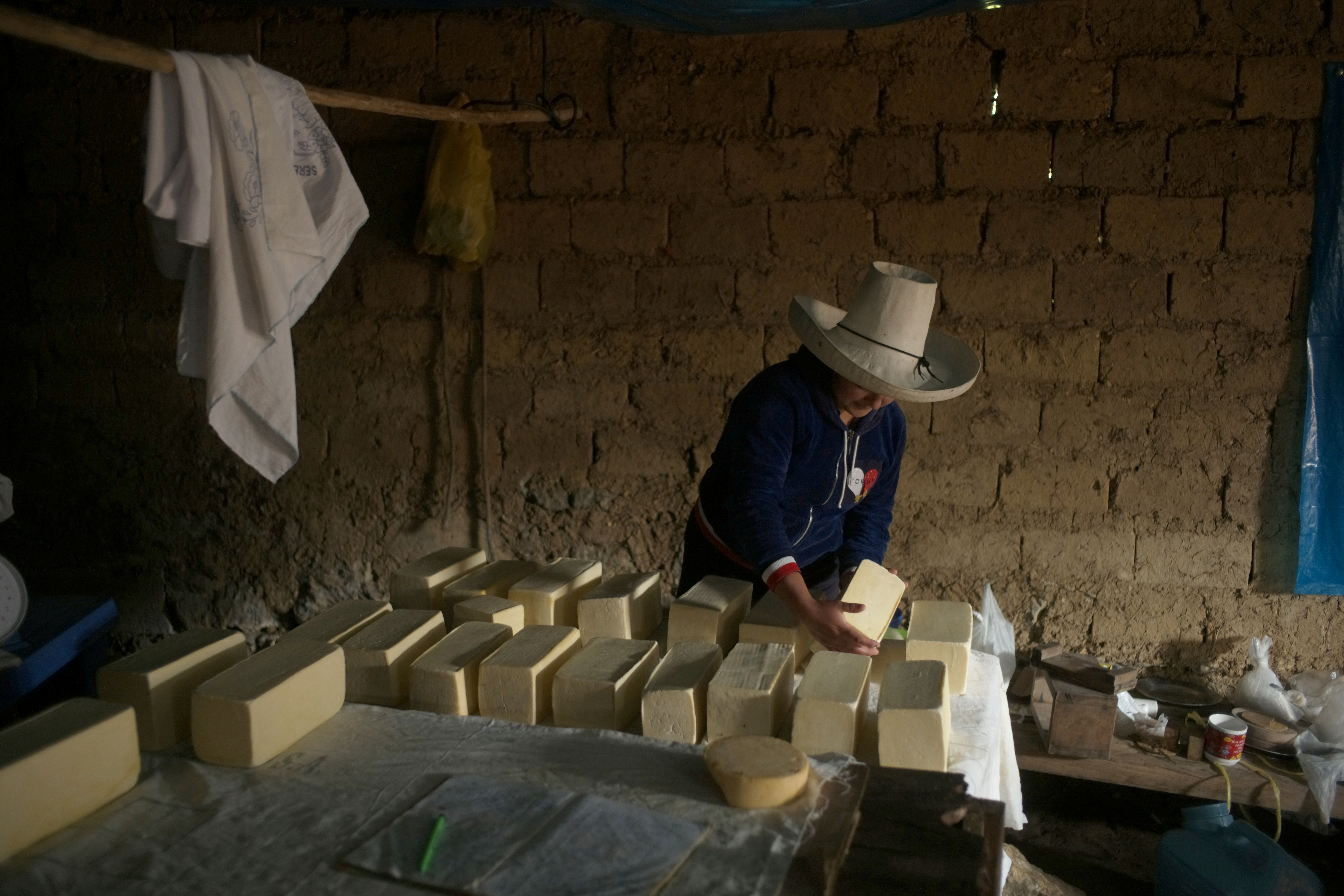 Luceli Banda Medina, a former student of Peru's presidential candidate Pedro Castillo, arranges blocks of cheese that she and her family made at home, in Puna, Peru June 3, 2021. Picture taken June 3, 2021. REUTERS/Alessandro Cinque